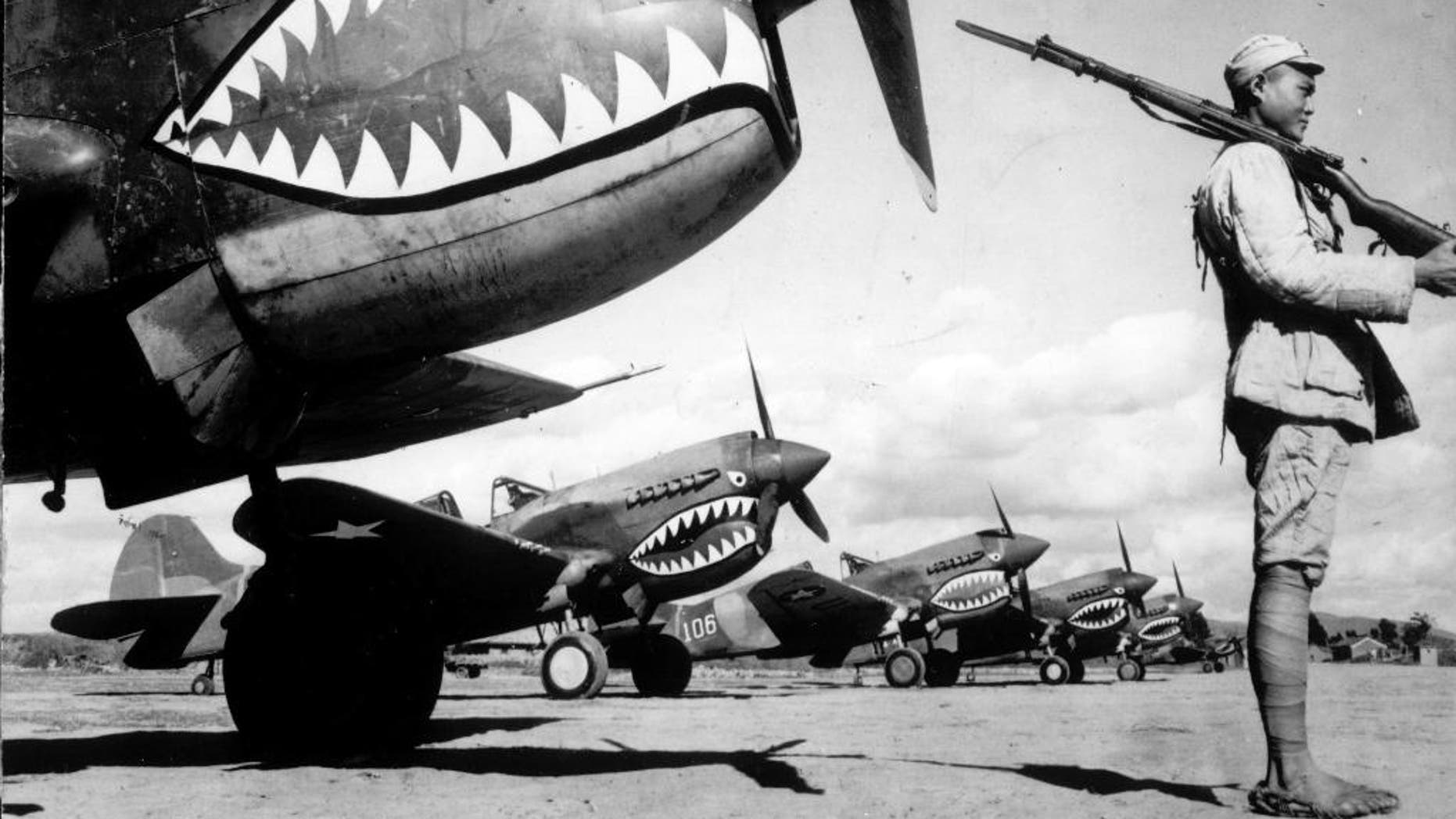 In this 1943 photo, guarded by a Chinese soldier, a squadron of Curtiss P-40 fighter planes, decorated with the typical shark face of the famed Flying Tigers, are lined up at an unknown airbase in China. An airfield in southern China from which the famed Flying Tigers took off to fight Japanese warplanes is being converted to battle a new enemy: drought. (AP Photo)