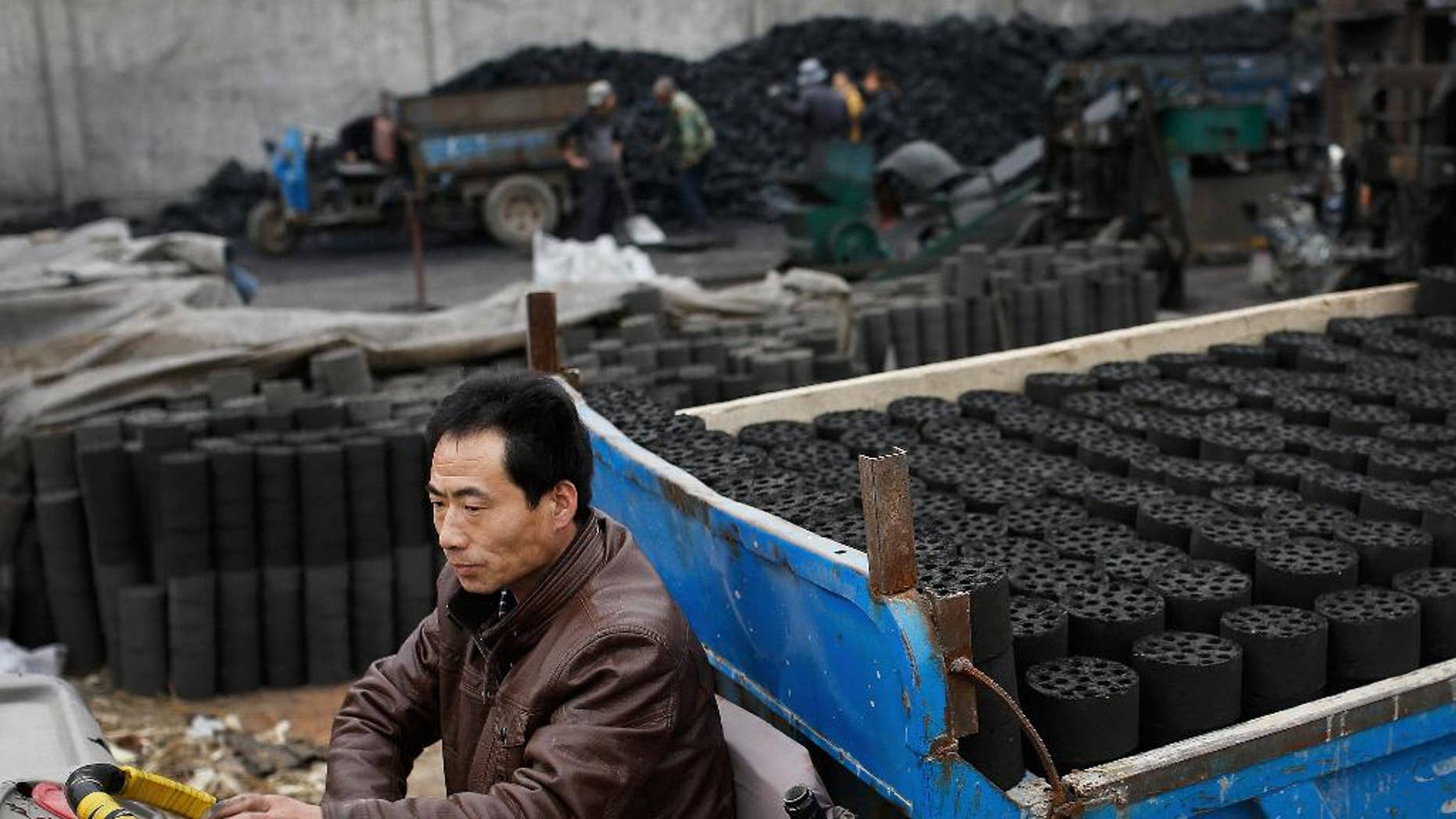 In this Nov. 27, 2014 photo, a man drives his tricycle cart loaded with coal briquettes as he leaves a coal process station in Tangxian in China's Hebei province. Coal production in China, the world's biggest coal-consuming nation, fell by 6 percent in the first four months of the year 2015 as the economy slows and the government makes a concerted push to reduce carbon emissions. The National Development and Reform Commission said Tuesday, May 26, 2015 that Chinese imports of coal also fell, plummeting 38 percent. (AP Photo/Andy Wong)