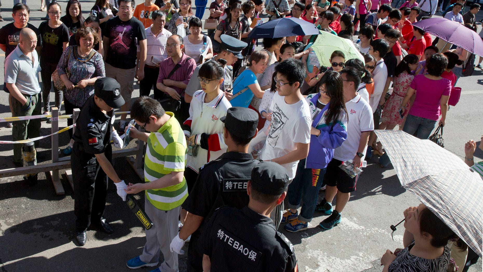 June 7, 2015 - A security guard uses a metal detector to check students arriving for the annual Gao Kao or national college entrance exam held at a school in Beijing. More than 9 million Chinese students will compete in the 2-day exams for around 7 million seats in the nation's colleges.