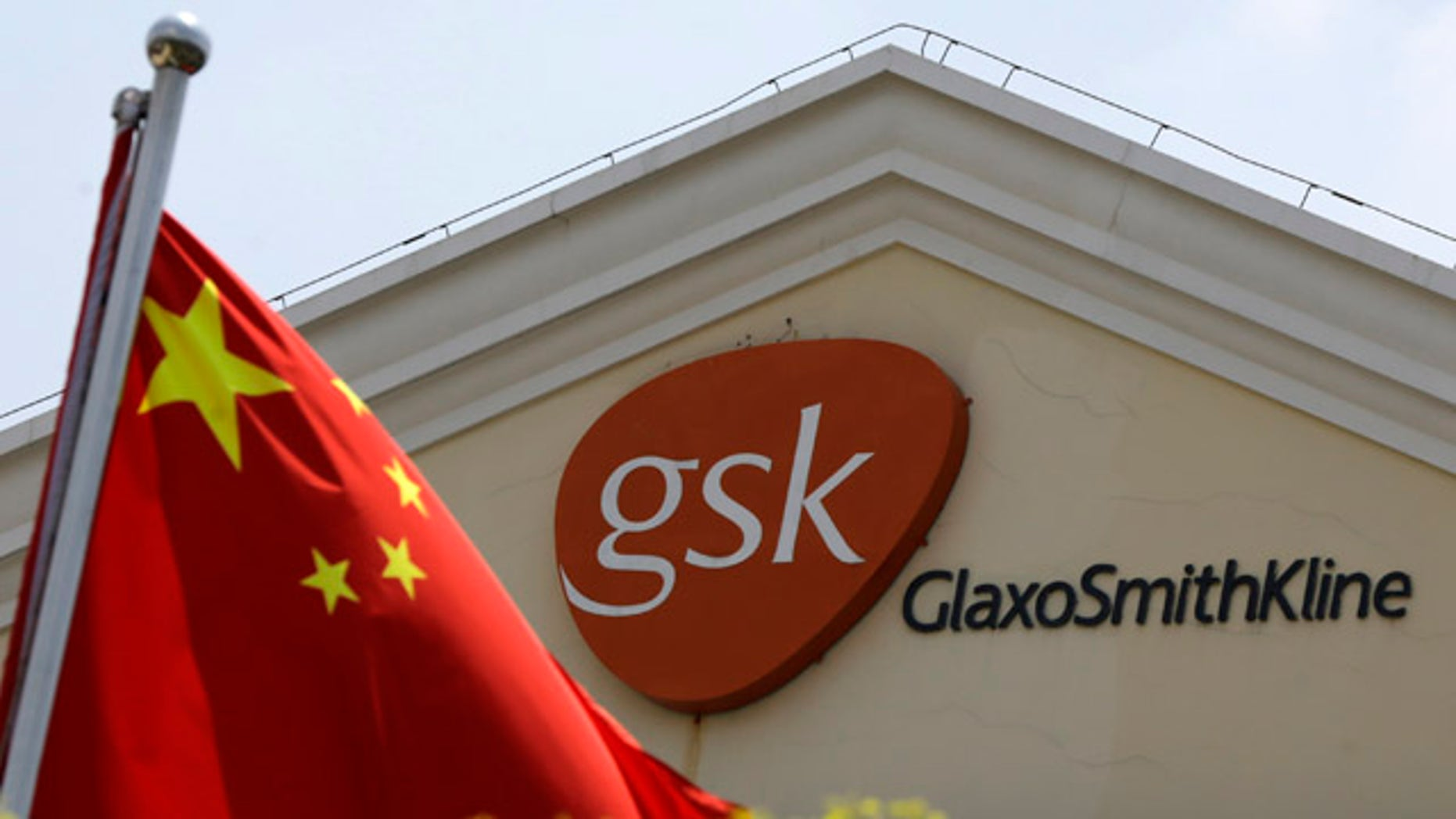 July 24, 2013: A Chinese flag is hoisted in front of a GlaxoSmithKline building in Shanghai, China. (AP Photo/Eugene Hoshiko, File)
