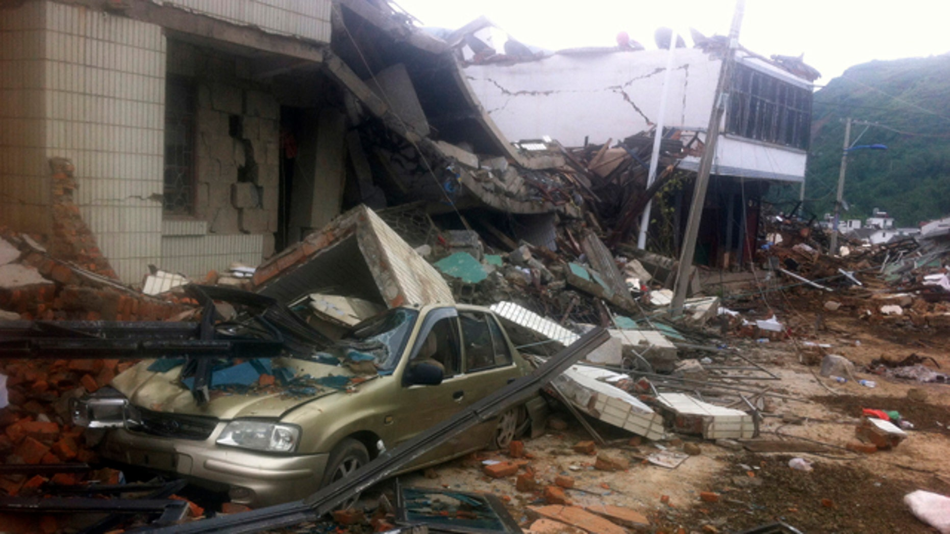 August 4, 2014: A car sits crushed by a collapsed building at the epicenter of an earthquake that struck the town of Longtoushan on Sunday, in Ludian County in southwest China's Yunnan Province. (AP Photo)