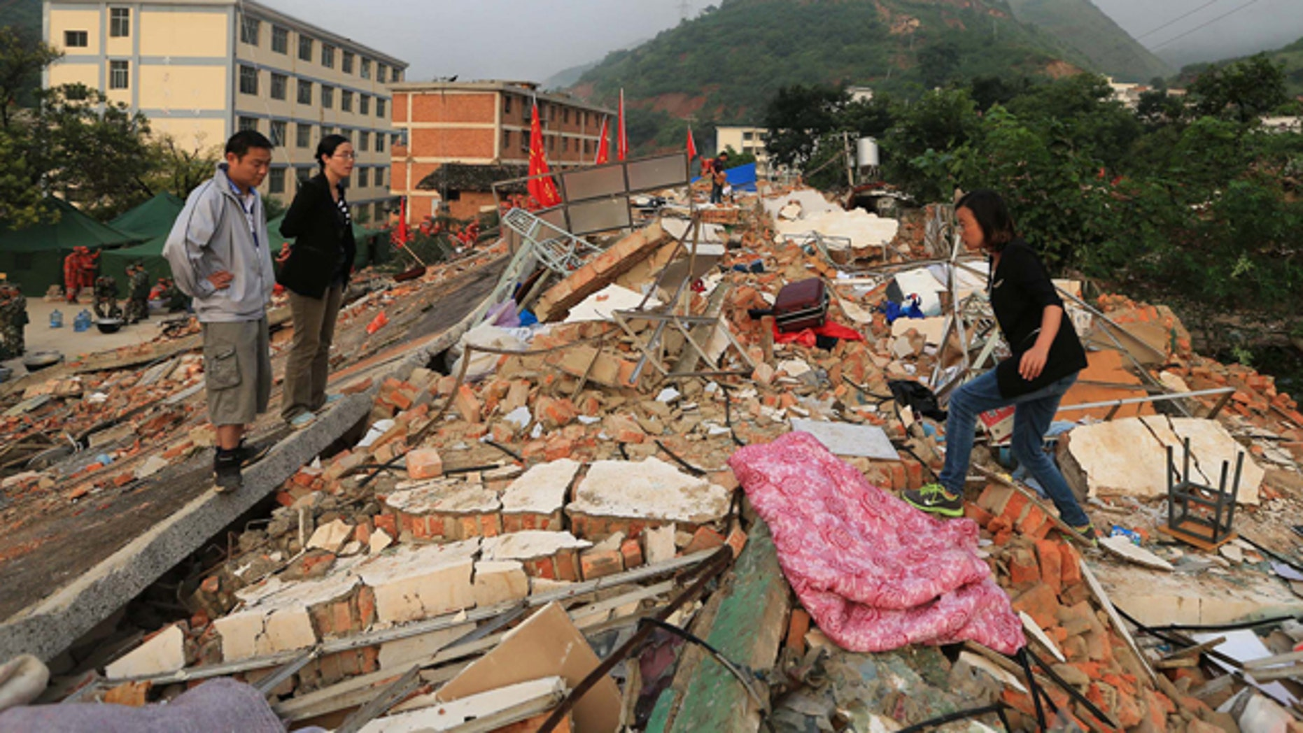 August 5, 2014: In this photo provided by China's Xinhua News Agency, teachers search for their belongings from collapsed dormitories at Longquan Middle School in Longtoushan town of Ludian county, southwest China's Yunnan Province. (AP Photo/Xinhua, Xing Guangli)