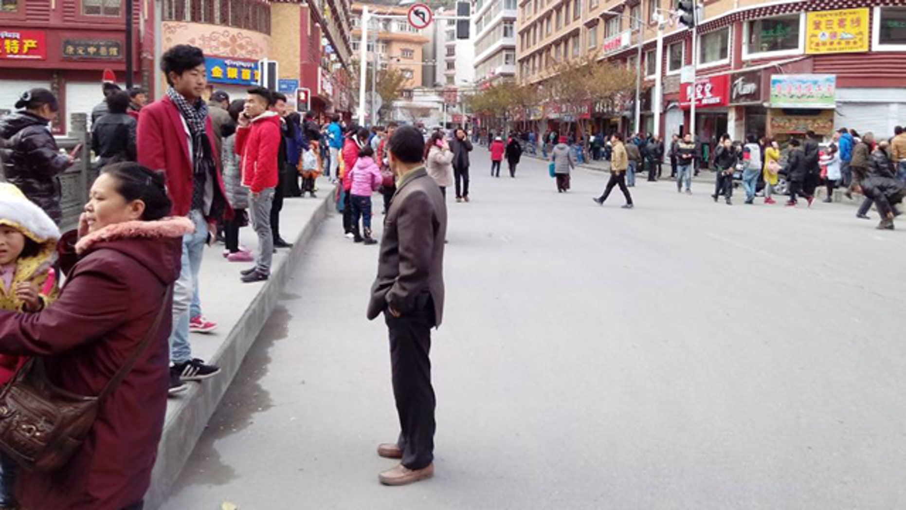 Nov. 22, 2014: In this photo released by China's Xinhua News Agency, locals stand outside after a quake hit Kangding County in Sichuan Province, China. (AP)