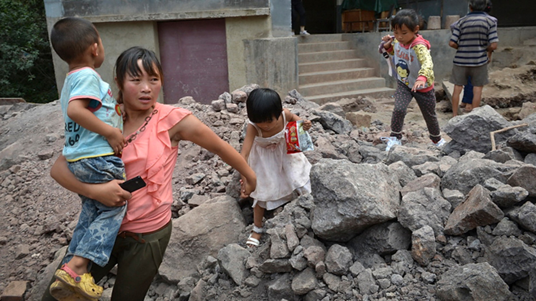 Sept. 8, 2012: A woman brings the children evacuate from an earthquake hit Luozehe town in Yiliang county in southwest China's Yunnan province.