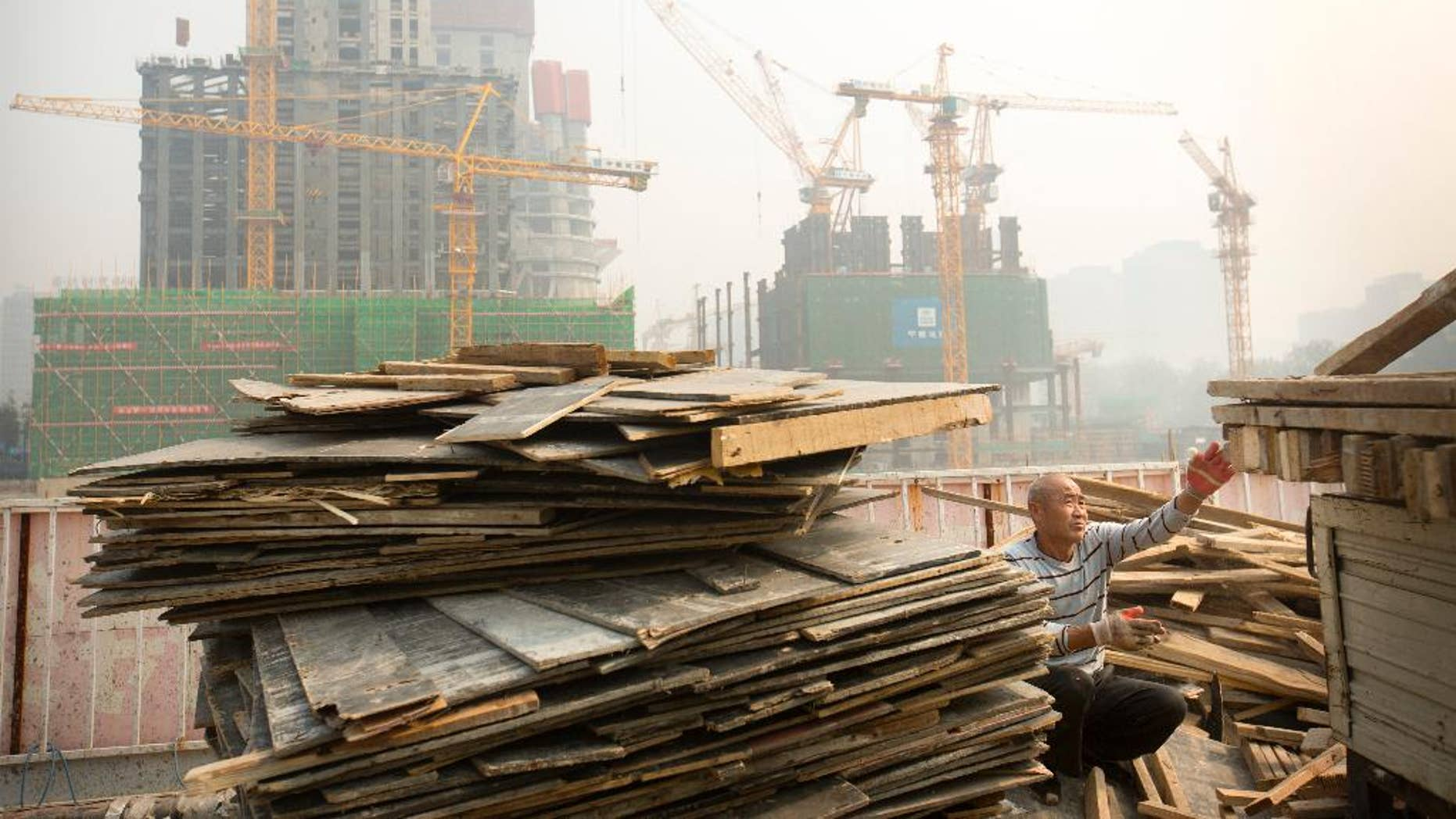 FILE - In this Oct. 6, 2015 file photo, a worker tosses boards onto the back of a truck at a construction site in Beijing. China's official data show economic growth slowing but skeptics say the downturn is much deeper than Beijing admits. The latest data Tuesday, Oct. 20, 2015,  showed growth in the world's No. 2 economy fell to a six-year low of 6.9 percent in the latest quarter. Private sector economists, however, say this year's true rate might be as low as 4 percent.(AP Photo/Mark Schiefelbein, File)