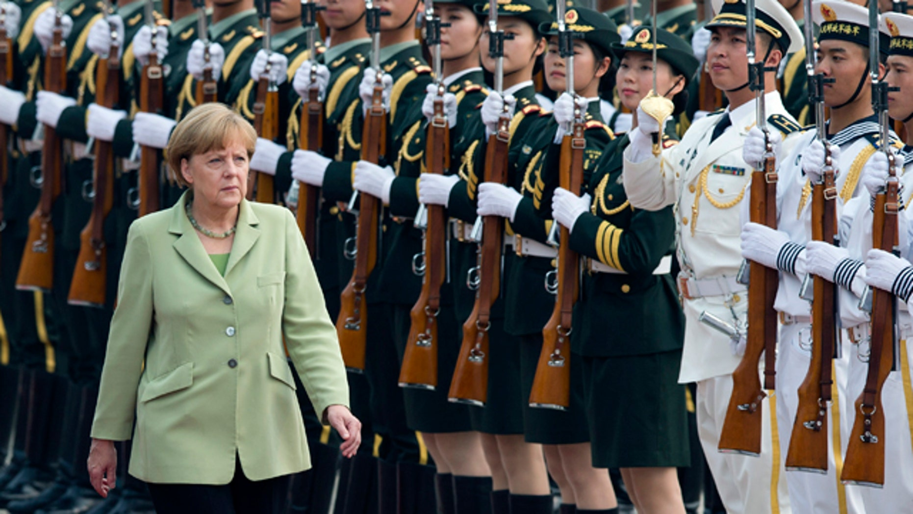 July 7, 2014: German Chancellor Angela Merkel reviews an honor guard during a welcome ceremony outside the Great Hall of the People in Beijing, China.(AP Photo/Andy Wong)