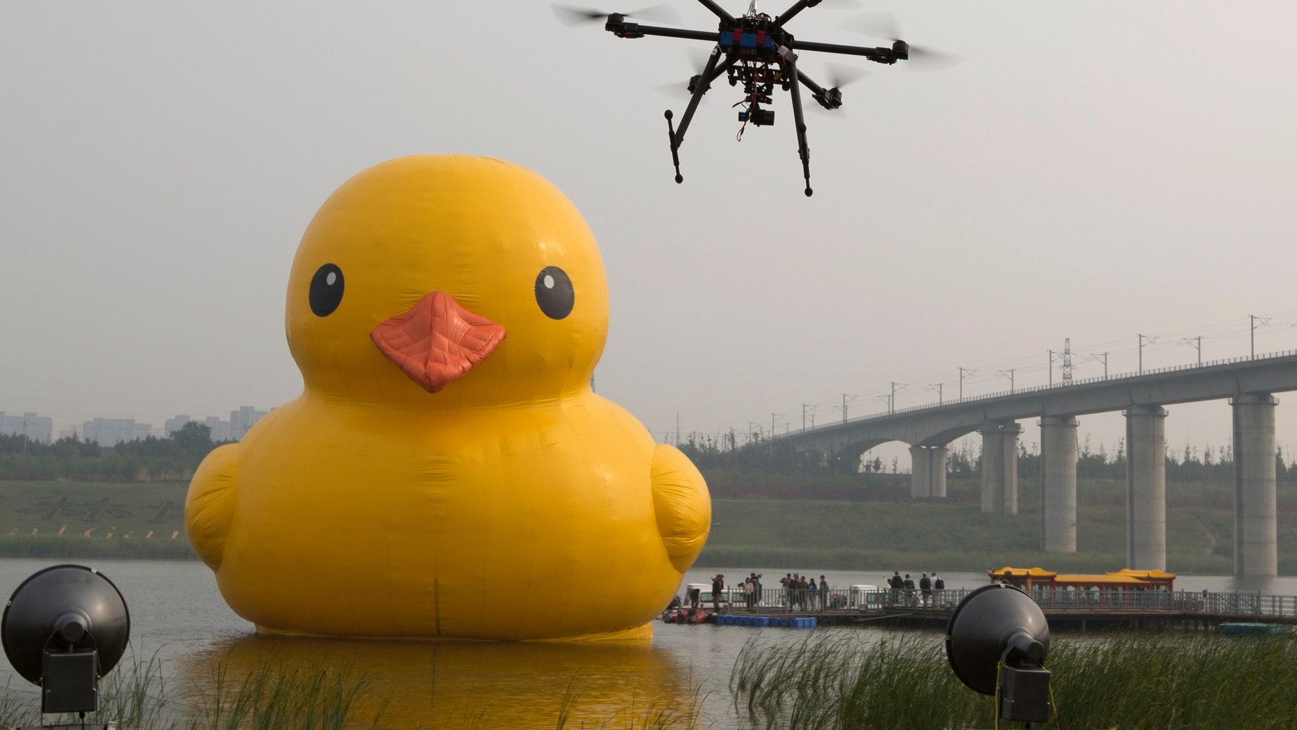 A drone camera hovers near a giant yellow rubber duck created by Dutch artist Florentijn Hofman as an art piece floating in an enclosed branch of Beijing's Yongding river in Beijing, China, Friday, Sept. 6, 2013. The 18-meter tall inflatable duck resembling a popular yellow rubber toy made its debut in Beijing on Friday after attracting wide attention in previous appearances in eight major cities around the world. (AP Photo/Ng Han Guan)