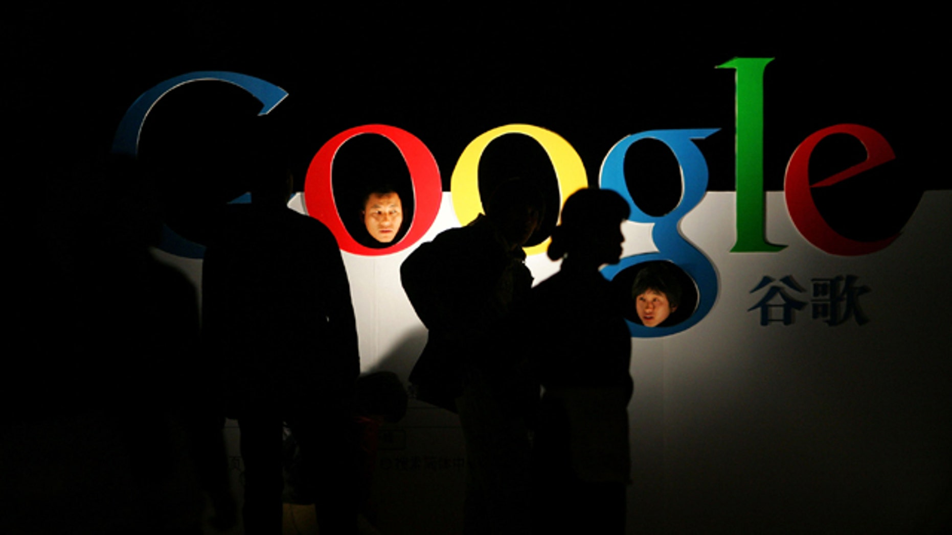 Chinese poke their heads through a Google logo shortly after Google debuts its Chinese Language brand name in the Beijing Hotel in Beijing. Google Inc. said Wednesday that its search engine has been partially blocked in the country.