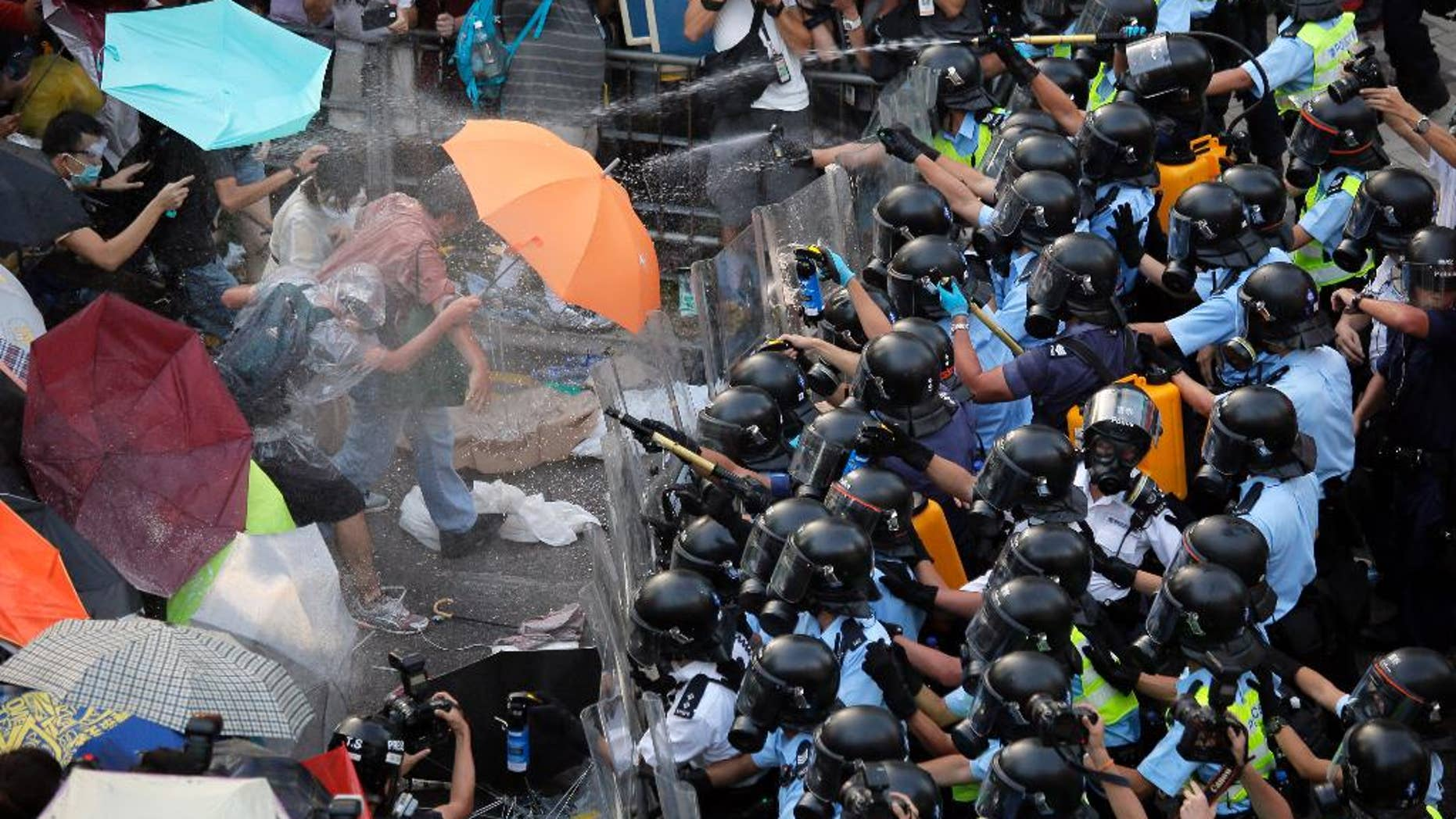 FILE - In this Sept. 28, 2014 file photo, riot police use pepper spray against protesters after thousands of people block a main road to the financial central district outside the government headquarters in Hong Kong. Ubiquitous images in Hong Kong media with masses of unarmed students fending off pepper spray with umbrellas could not contrast more starkly with mainland China's virtual blackout of news about the territory's pro-democracy protests. (AP Photo/Vincent Yu, File)