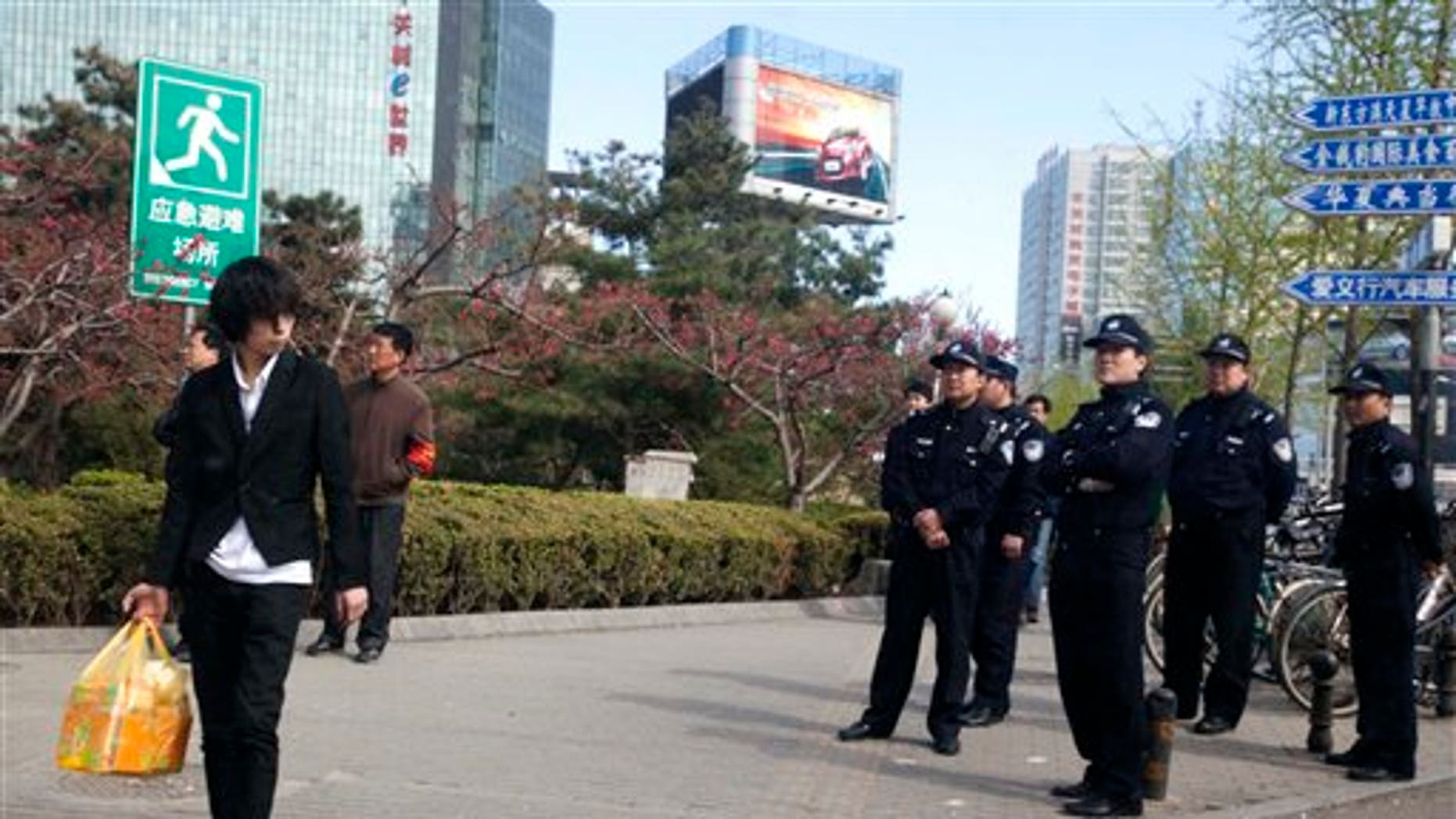 April 10: Chinese police officers watch an area near a building that leaders of the unregistered Shouwang house church had told parishioners to gather in Beijing, China.  Beijing police on Sunday detained at least a dozen worshippers from the Christian house church who were trying to hold services in a public space after they were evicted from their usual place of worship. (AP)
