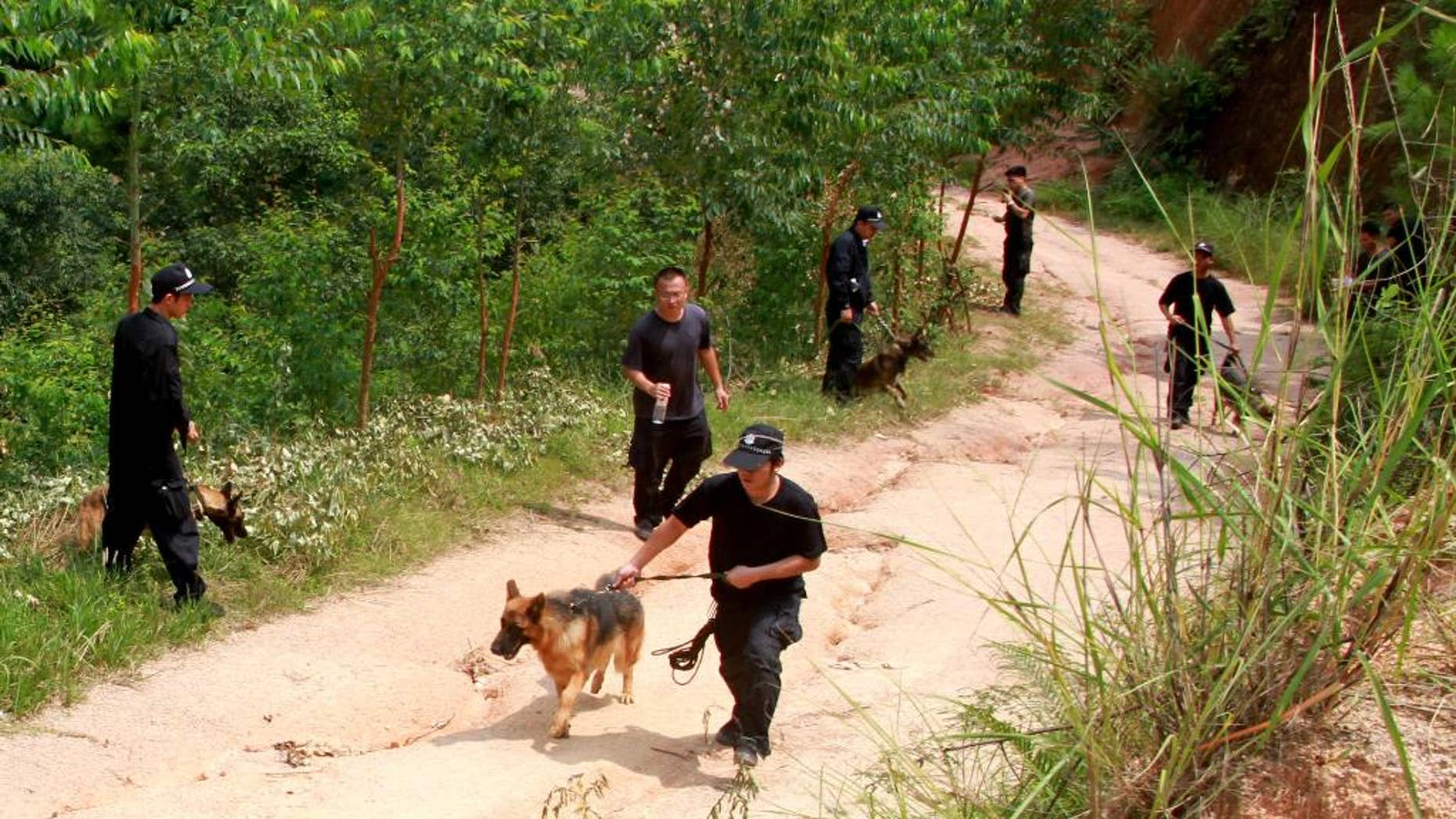 In this photo released by China's Xinhua news agency, policemen use sniffer dogs to search for a man of stabbing four elementary school students, in Pingshan Town of Lingshan County, south China's Guangxi Zhuang Autonomous Region, Friday, Sept. 26, 2014. The man fatally stabbed four elementary school students Friday while they were on their way to school, the latest of several slashing attacks targeting schoolchildren over the past decade. The county government said on its website that three of the children were killed instantly and that one died later in hospital. Officials said police are searching for 56-year-old suspect, but gave no other details. (AP Photo/Xinhua, Zhang Ailin) NO SALES