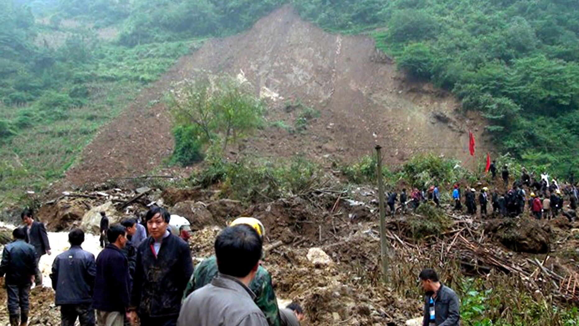 In this photo taken Thursday Oct. 4, 2012, residents gather at a landslide in Yiliang county in southwest China's Yunnan province. All 18 elementary school students buried in the landslide were confirmed dead Friday, while one other person remained missing a day after the hillside collapsed and smothered part of a village in mountainous southwestern China. (AP Photo) CHINA OUT