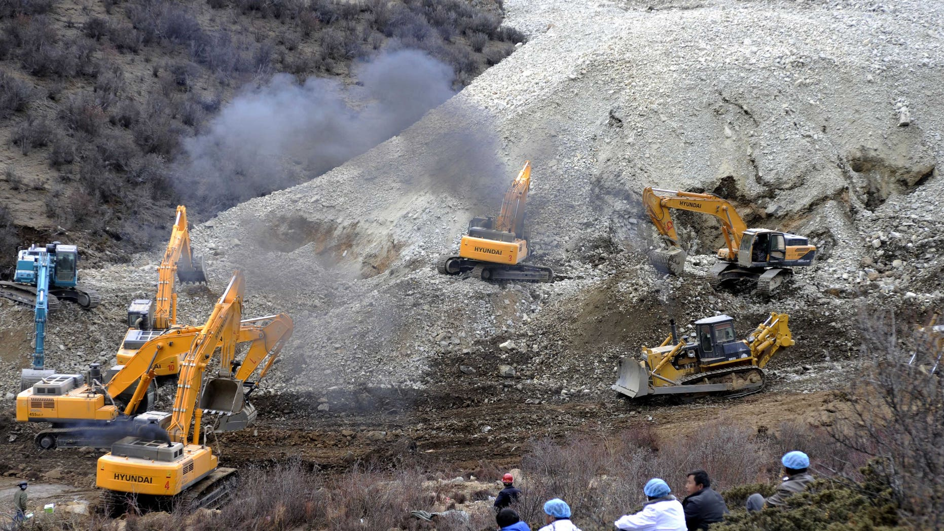 March 29, 2013 - Earthmovers remove rocks and mud on the scene where a landslide hit a mining area in Maizhokunggar County of Lhasa, southwest China's Tibet Autonomous Region.
