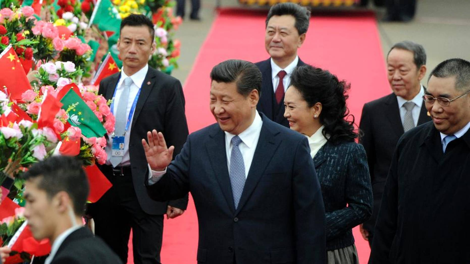 In this photo provided by China's Xinhua News Agency, Chinese President Xi Jinping, center, and his wife Peng Liyuan, center right,  wave as they arrive at the international airport in Macau, south China, Friday, Dec. 19, 2014. Chinese President Xi is in Macau to attend celebrations marking the 15th anniversary of its return to China which falls on Saturday, Xinhua reported. (AP Photo/Xinhua, Cheong Kam Ka) NO SALES