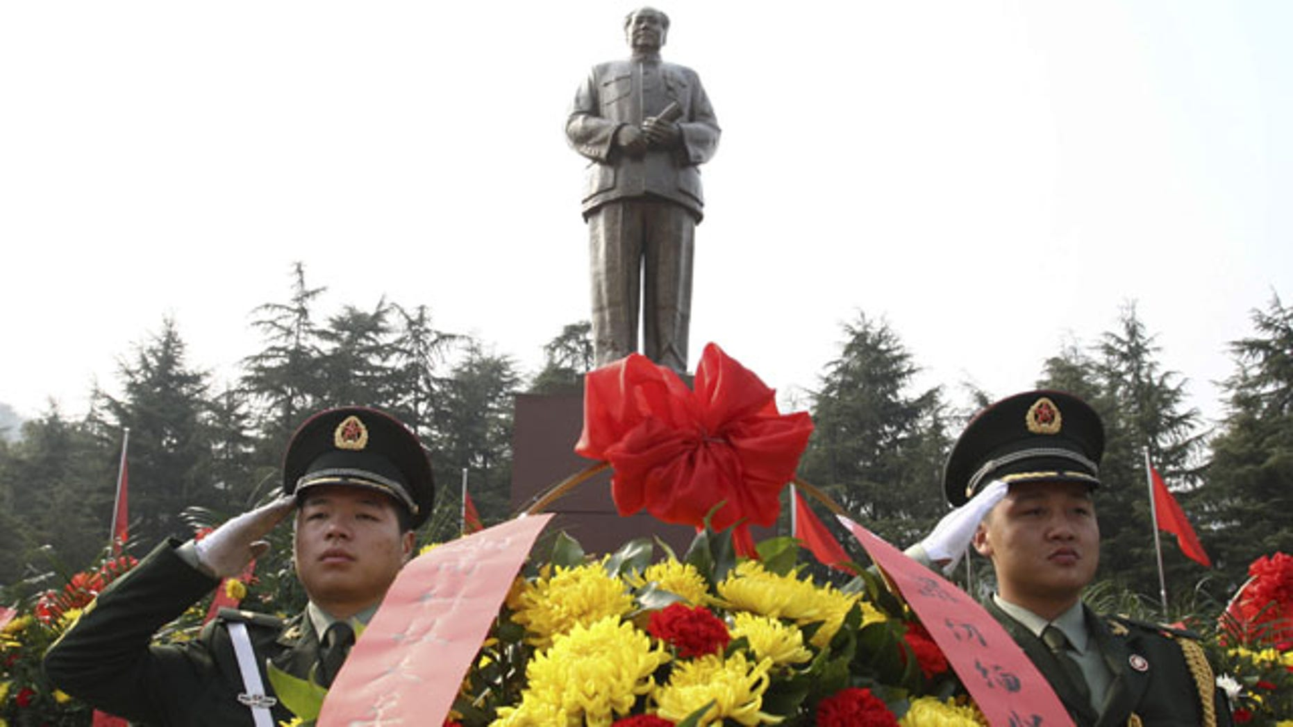 December 25, 2013: Security guards salute near wreaths in front of a statue of the late Communist leader Mao Zedong in Shaoshan, Mao's hometown, in southern China's Hunan province. (AP Photo)