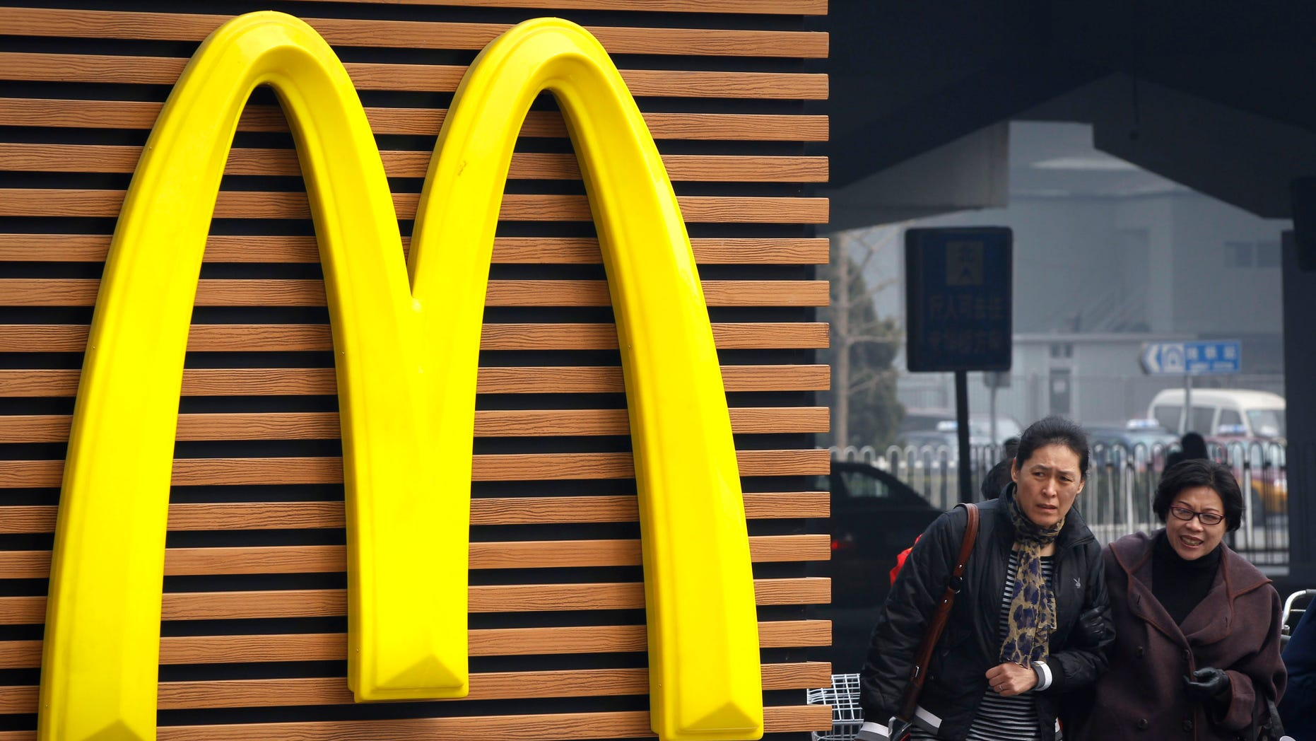 Mar. 16, 2012: Chinese women walk past a McDonald's sign in Beijing.
