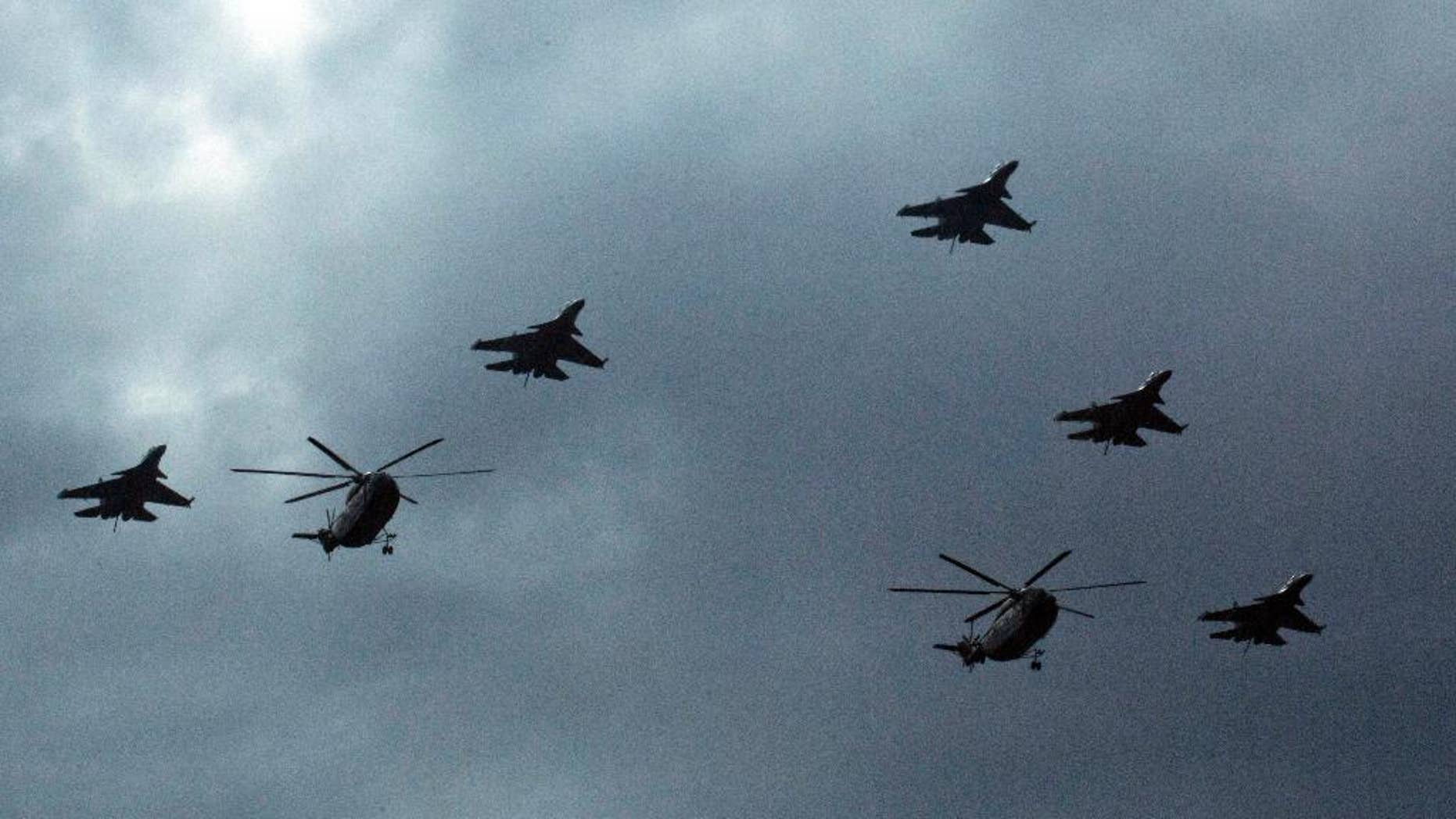 Chinese military helicopters and fighter jets take part in rehearsals ahead of the Sept. 3 military parade to commemorate the end of World War II in Beijing, Sunday, Aug. 23, 2015. China is ramping up publicity for its upcoming massive military parade but officials still aren't saying what other countries are taking part. (AP Photo/Ng Han Guan)