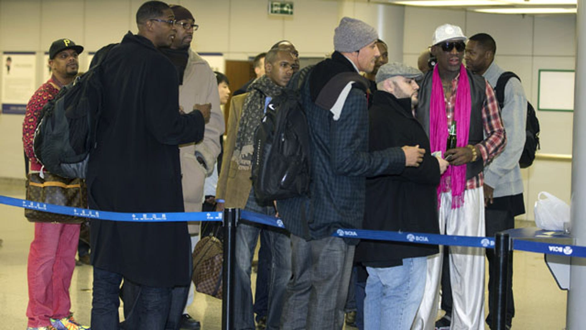 January 6, 2014: Former NBA basketball player Dennis Rodman, right, and former NBA players wait at the departure hall of Beijing International Capital Airport. Rodman says he's going forward with an exhibition game including former NBA players in North Korea because he wants to connect with its people and let others know the sheltered communist country isn't so bad. (AP Photo/Andy Wong)
