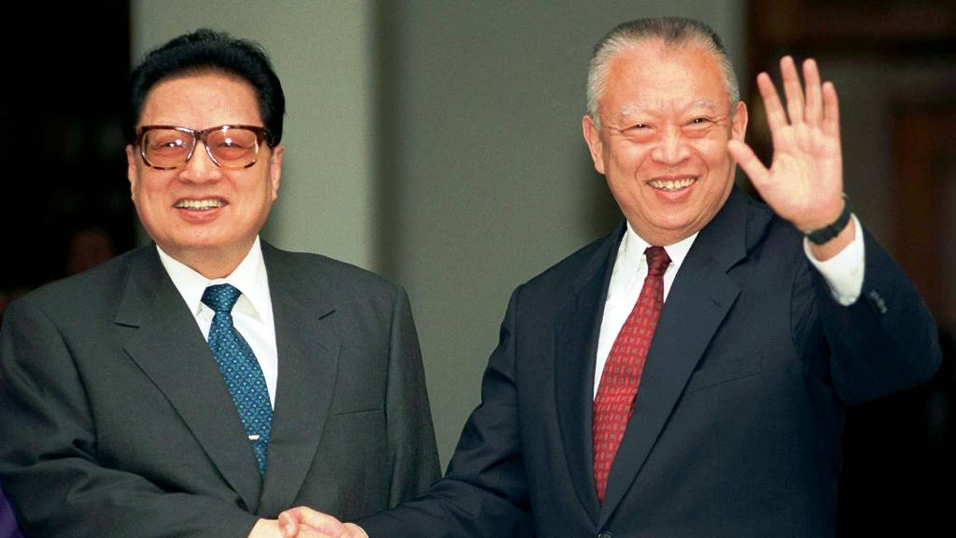 FILE - In this Feb.11, 1998 file photo, then Hong Kong leader Tung Chee-hwa, right, waves to photographers while shaking hands with then China's legislative leader Qiao Shi outside Government House in Hong Kong. Qiao Shi, a senior Communist Party official and chairman of China's legislature in the 1990s, died Sunday, June 14, 2015 at the age of 91, state media said. (AP Photo/Anat Givon, File)