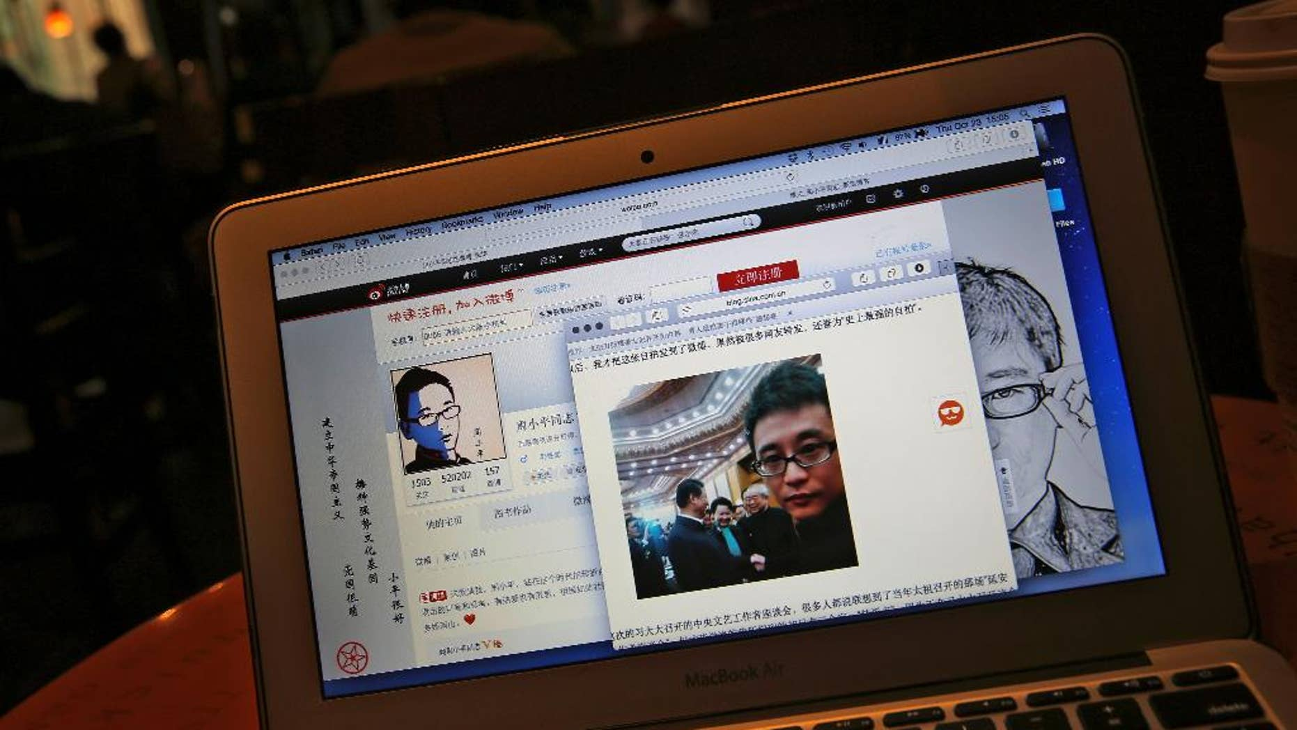 """This screen shot shows Chinese Patriotic Blogger, Zhou Xiaoping's Sina Weibo account and his selfie near Chinese President Xi Jinping with officials at the Great Hall of the People, in his blog, in Beijing, China Thursday, Oct. 23, 2014. He shook hands with President Xi Jinping earlier this month in a rare literature and arts meeting, where the 33-year-old blogger sat along with Chinese novelist and Nobel literature laureate Mo Yan. Zhou said in his blog that Xi told him to keep spreading """"positive energy on the Internet."""" (AP Photo/Andy Wong)"""