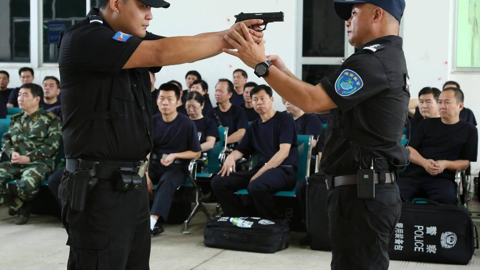 FILE - In this April 25, 2014 file photo, a police training officer, right, guides a trainee during a weapons training session for police officers in Haikou, in southern China's Hainan province.  Newly granted power for normal Chinese police officers to carry a firearm, has raised calls for a full independent investigation, after a police officer killed an unarmed traveler in front of his elderly mother and three small children at a train station, the Public Security Ministry said Tuesday May 12, 2015, after several shootings by police were never fully accounted for, according to Zhao Chu, a Shanghai-based independent commentator.  (Chinatopix via AP, File) CHINA OUT