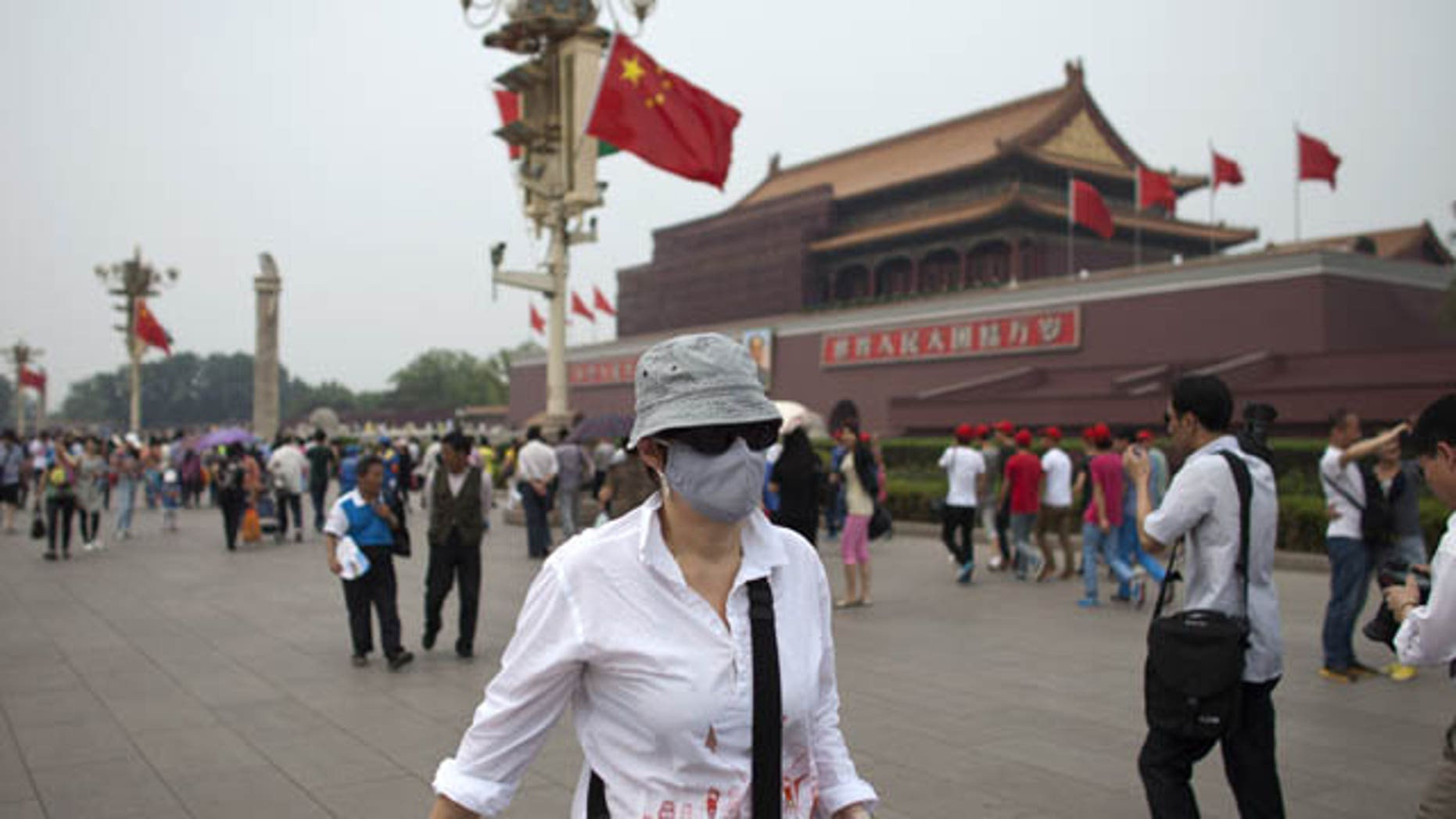 FILE - In this May 7, 2013 file photo, a foreign tourist wearing a mask walks in front of Tiananmen Gate on a polluted day in Beijing, China. (AP Photo)