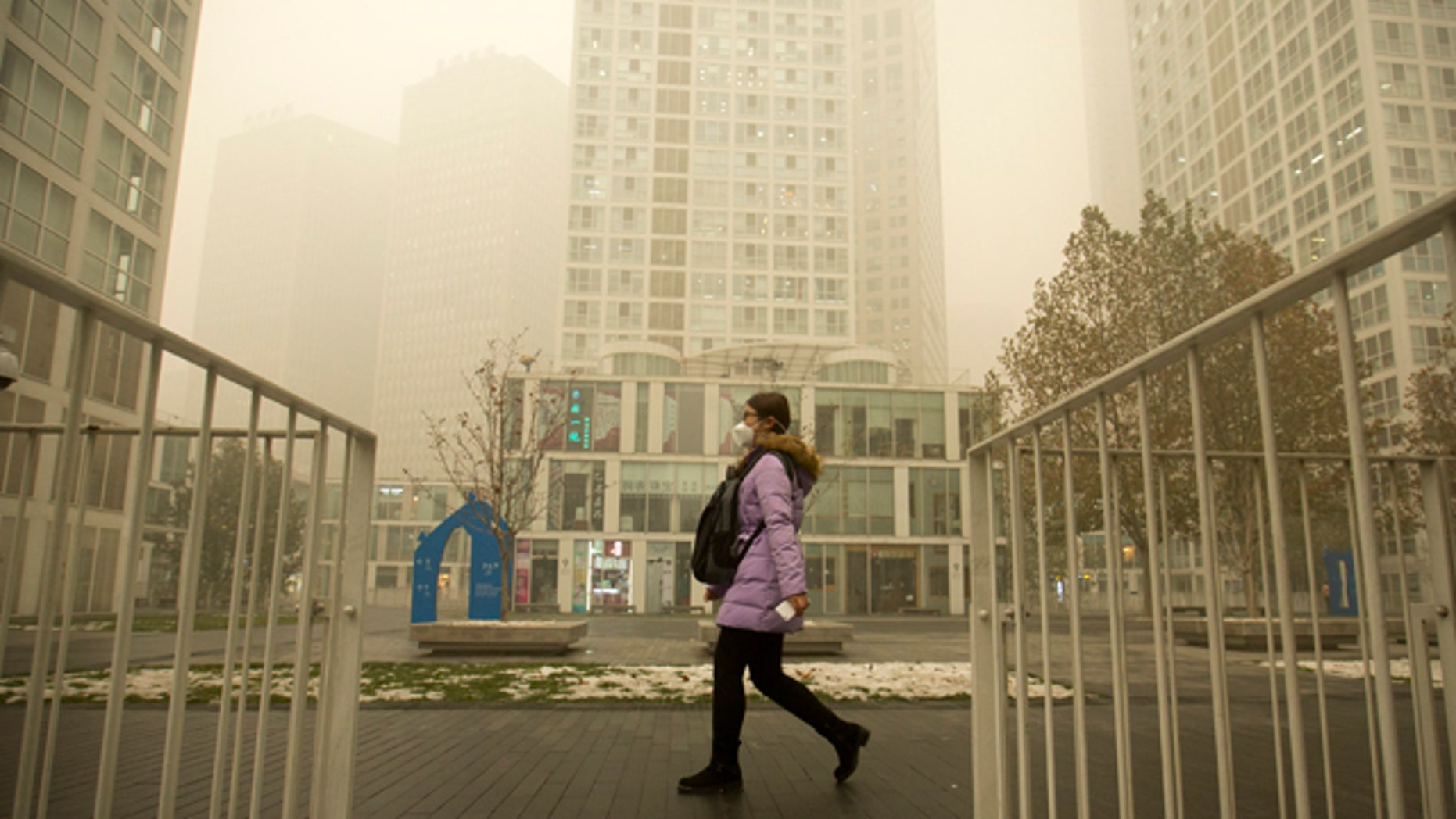 Dec. 1, 2015: A woman wearing a face mask walks through a shopping and office complex amid heavy pollution and fog in Beijing. (AP Photo/Mark Schiefelbein)