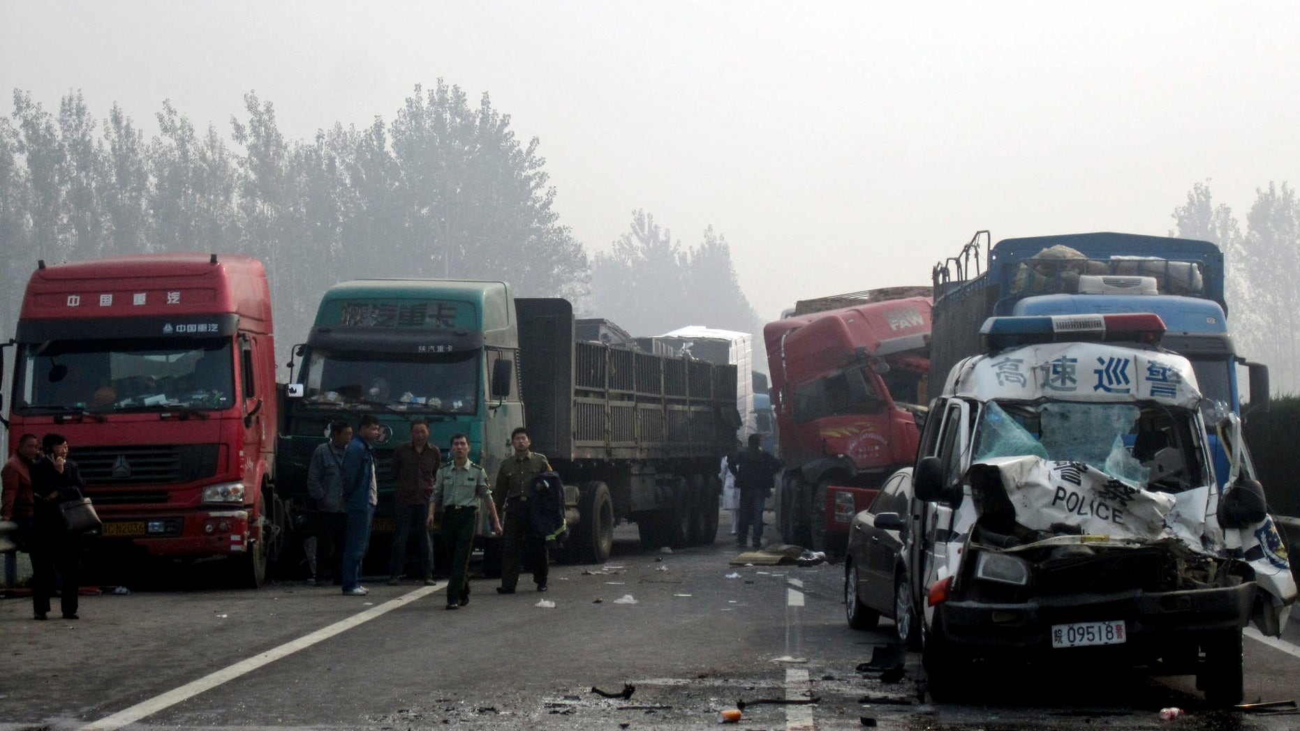 Oct. 7, 2011: People look at the damaged vehicles piled up on a highway road in Huaibei in central China's Anhui province. Three major road accidents in China killed at least 56 people on the last day of a weeklong holiday, including 35 people who died after a bus collided with a car on a northern expressway, state media reported Saturday.