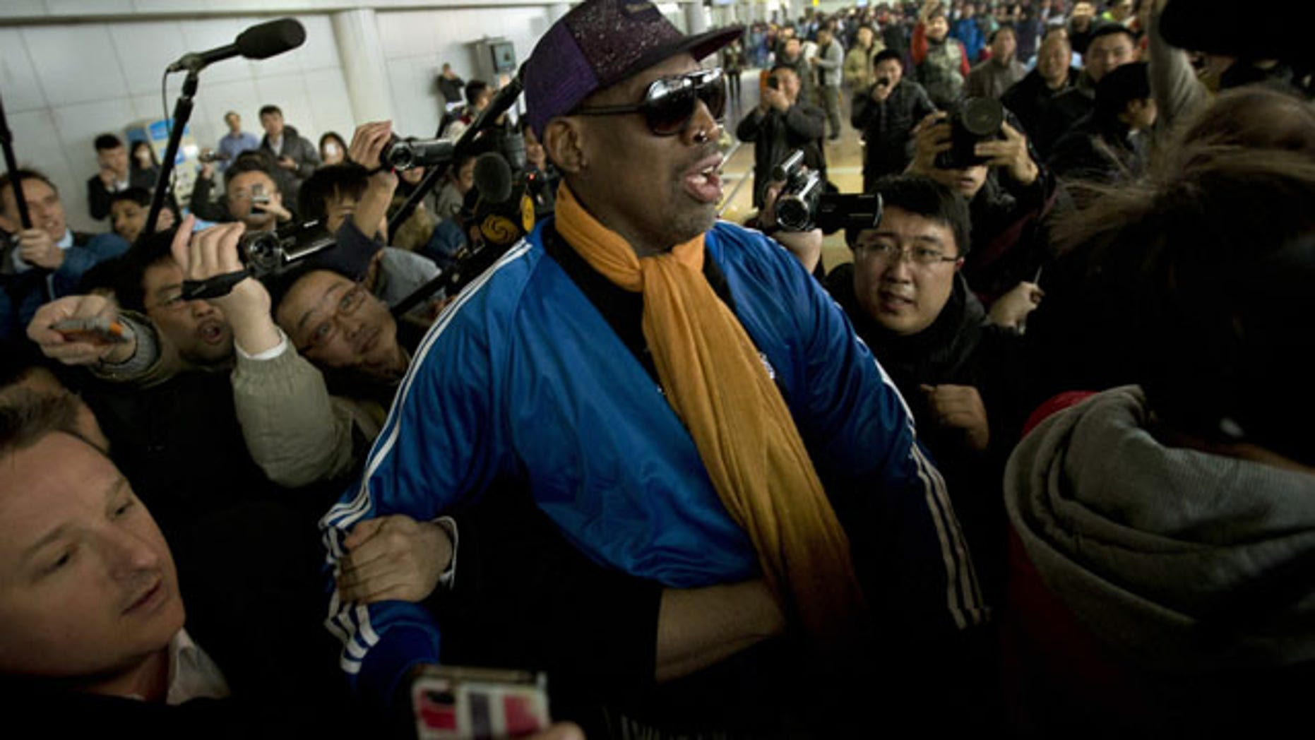 January 13, 2014: Former NBA basketball player Dennis Rodman is followed by journalists as he arrives at the Capital International Airport in Beijing from Pyongyang. A squad of former basketball stars led by Rodman had a friendly game with North Korean basketball players in Pyongyang. (AP Photo/Alexander F. Yuan)