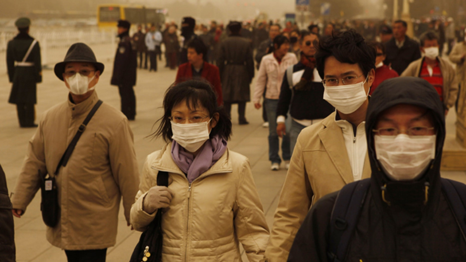 Tourists and residents wear masks as they visit Tiananmen gate during a sandstorm in Beijing, China, Monday, March 22, 2010.
