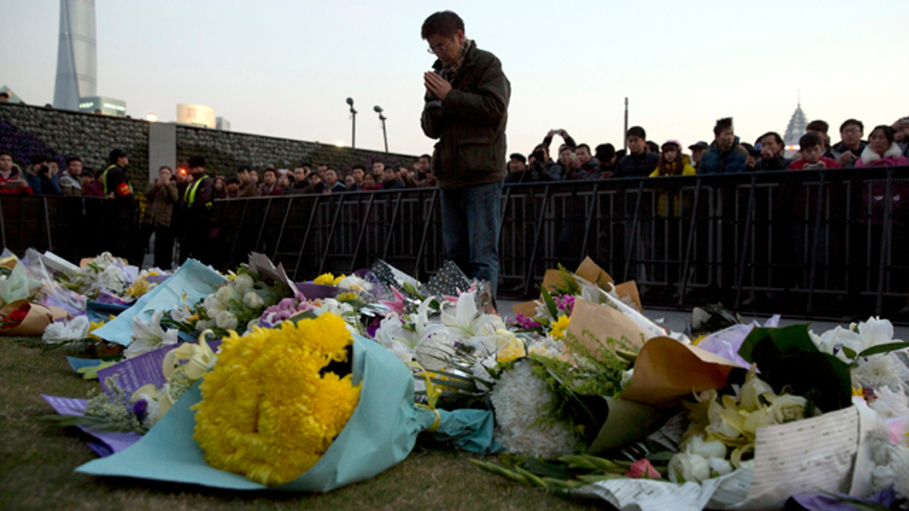 FILE - In this Thursday, Jan. 1, 2015 file photo, a man prays after laying flowers at the site of a New Years Eve deadly stampede in Shanghai. (AP Photo/Ng Han Guan, File)