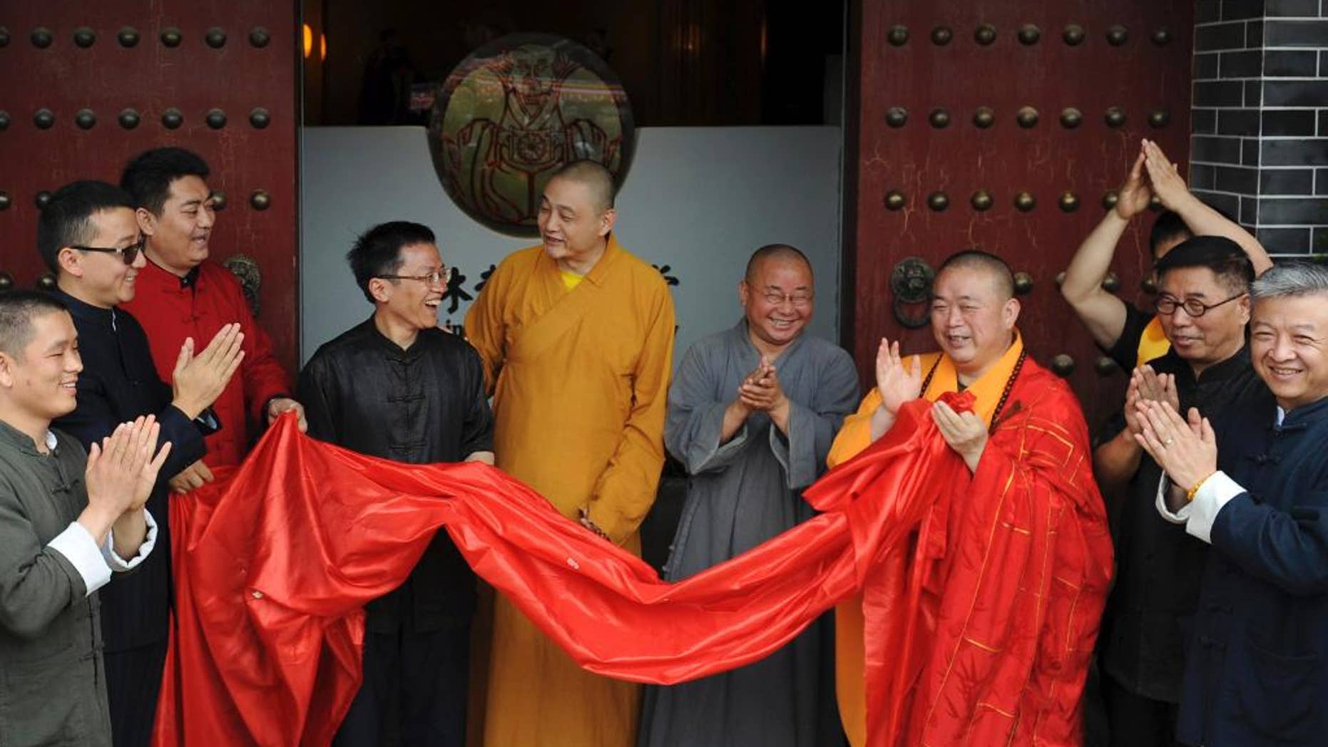 In this photo taken Sunday June 28, 2015, Shi Yongxin, third from right in yellow and red robes, abbot of the Shaolin Temple, attends the opening ceremony of an urban zen center named Shaolin Chan Hall in Xi'an in northwest China's Shaanxi province.  Chinese authorities are investigating allegations of misbehavior made online against the controversial abbot of China's famed Shaolin Temple. (Chinatopix Via AP) CHINA OUT