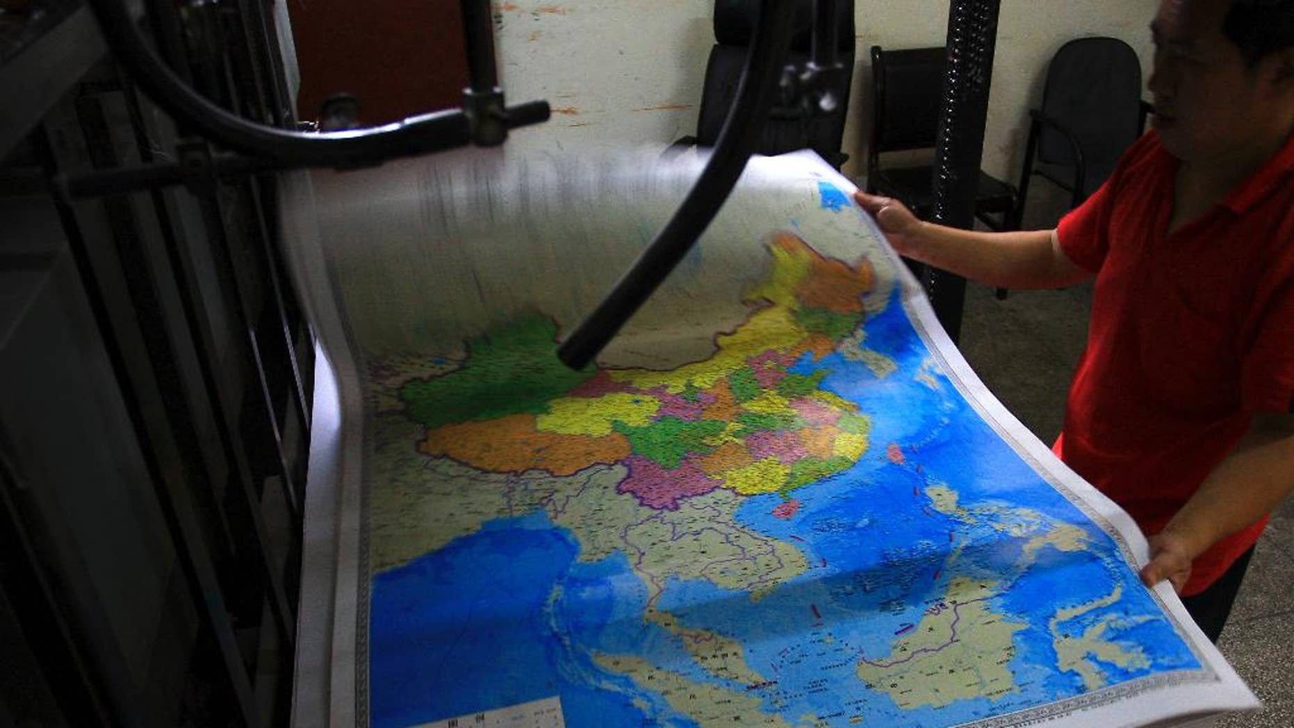 In this June 27, 2014 photo, a printing worker holds a new officially approved map of China that includes the islands and maritime area that Beijing claims in the South China Sea, at a factory in Changsha in south China's Hunan province.  China has again rejected an attempt by the Philippines to challenge its territorial claims over the South China Sea through international arbitration, releasing a lengthy paper a week before the Dec. 15, 2014 deadline for China to respond to the case. China prefers to settle its disputes with discussions with the countries directly involved. But the Philippines has filed a case with an international tribunal.(AP Photo) CHINA OUT
