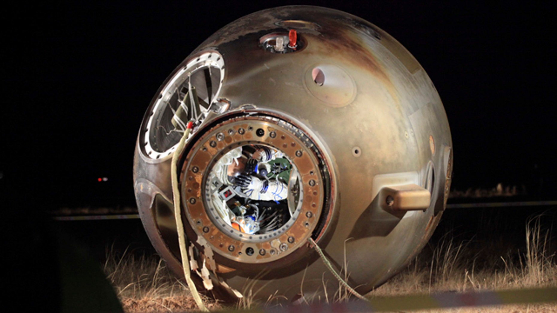 Nov. 17, 2011: A technician inspects the re-entry capsule of China's Shenzhou 8 spacecraft, which lies on its side with its hatch opened at a landing site in Siziwang Banner in north China's Inner Mongolia Autonomous Region. The unmanned Chinese spacecraft returned to Earth on Thursday night after it docked twice with an orbiting module in preparation for the country launching its own space station.
