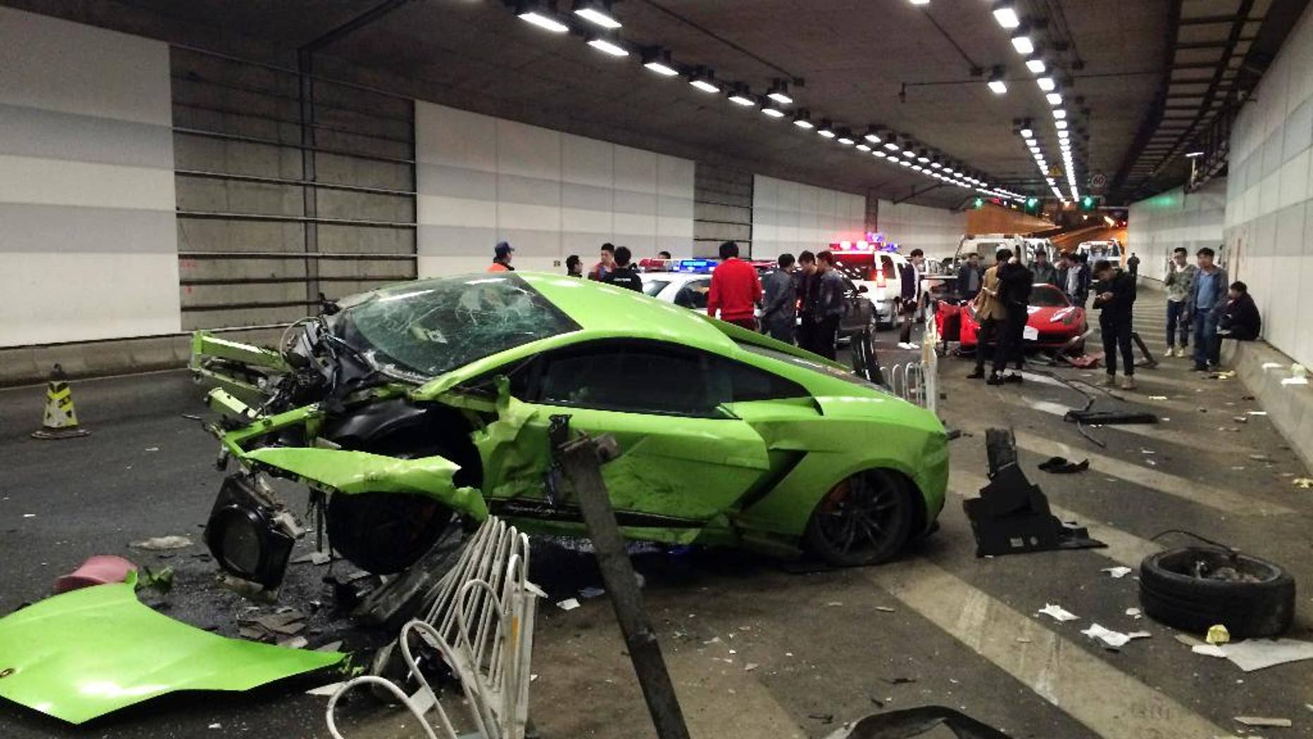 In this April 12, 2015 photo, policemen and bystanders check on a damaged Lamborghini, foreground, after it collided with a Ferrari in a tunnel in Beijing, China. A Beijing court on Thursday, May 21 sentenced two young men to up to five months in jail for dangerous driving, a month after they crashed their supercars in a late-night race through Beijing. (Chinatopix via AP) CHINA OUT