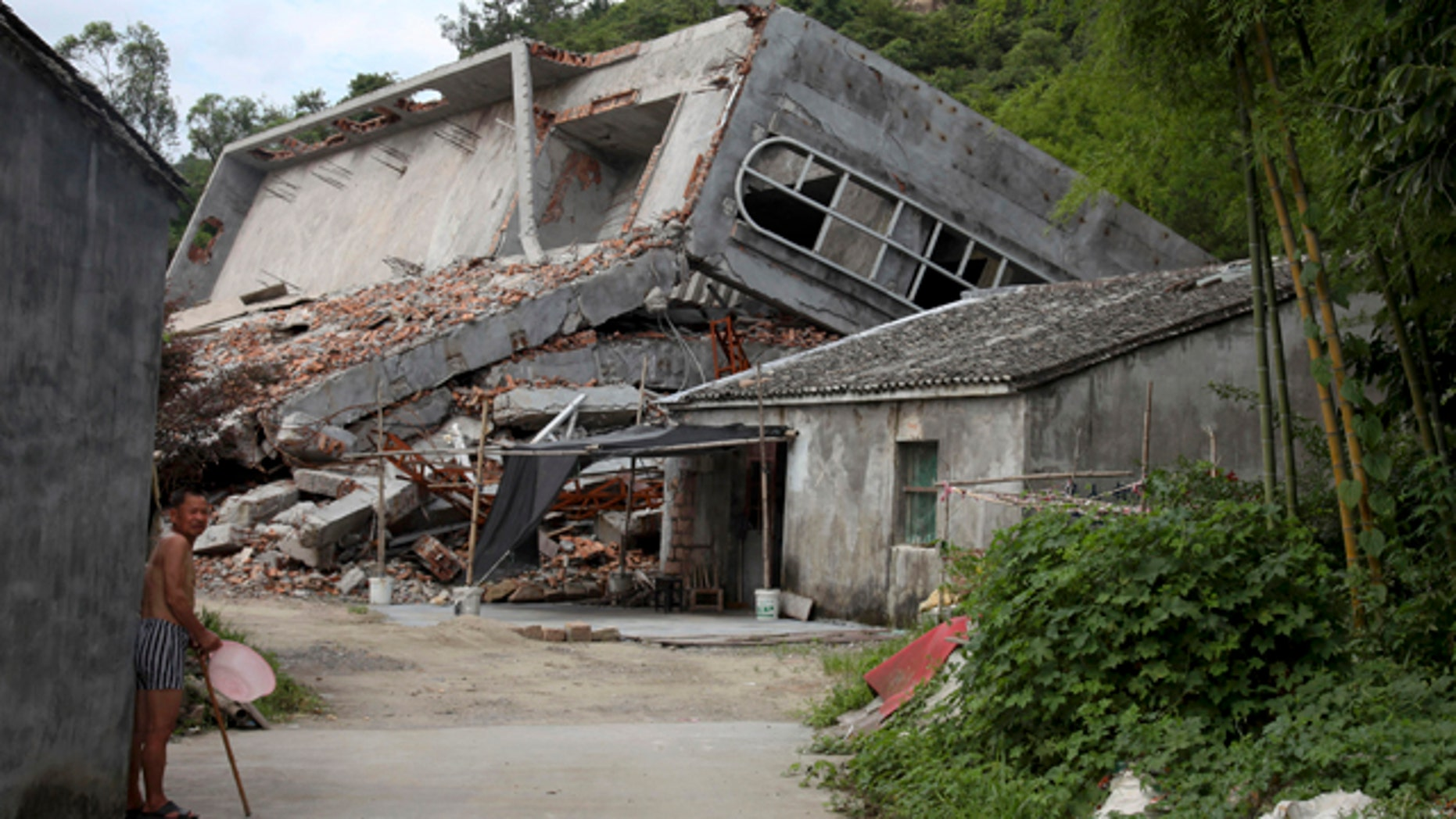 July 16, 2014: A man stands near the razed remains of a Catholic church in a village in Pingyang county of Wenzhou in eastern China's Zhejiang province. Across Zhejiang province, which hugs Chinas rocky southeastern coast, authorities have toppled, or threatened to topple, crosses at more than 130 churches. (AP Photo/Didi Tang)