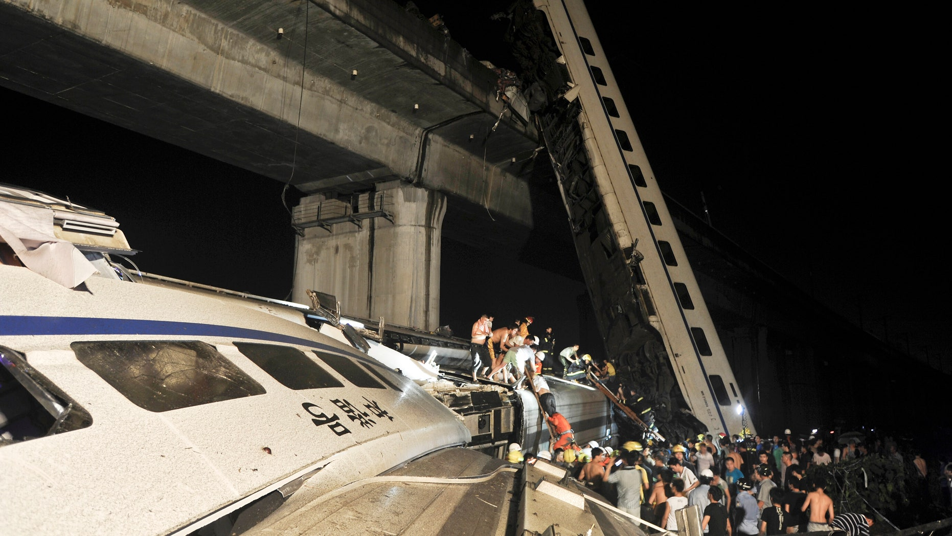 Emergency workers and people work to help passengers from the wreckage of train after two carriages from a high-speed train derailed and fell off a bridge in Wenzhou in east China's Zhejiang province Saturday July 23, 2011.