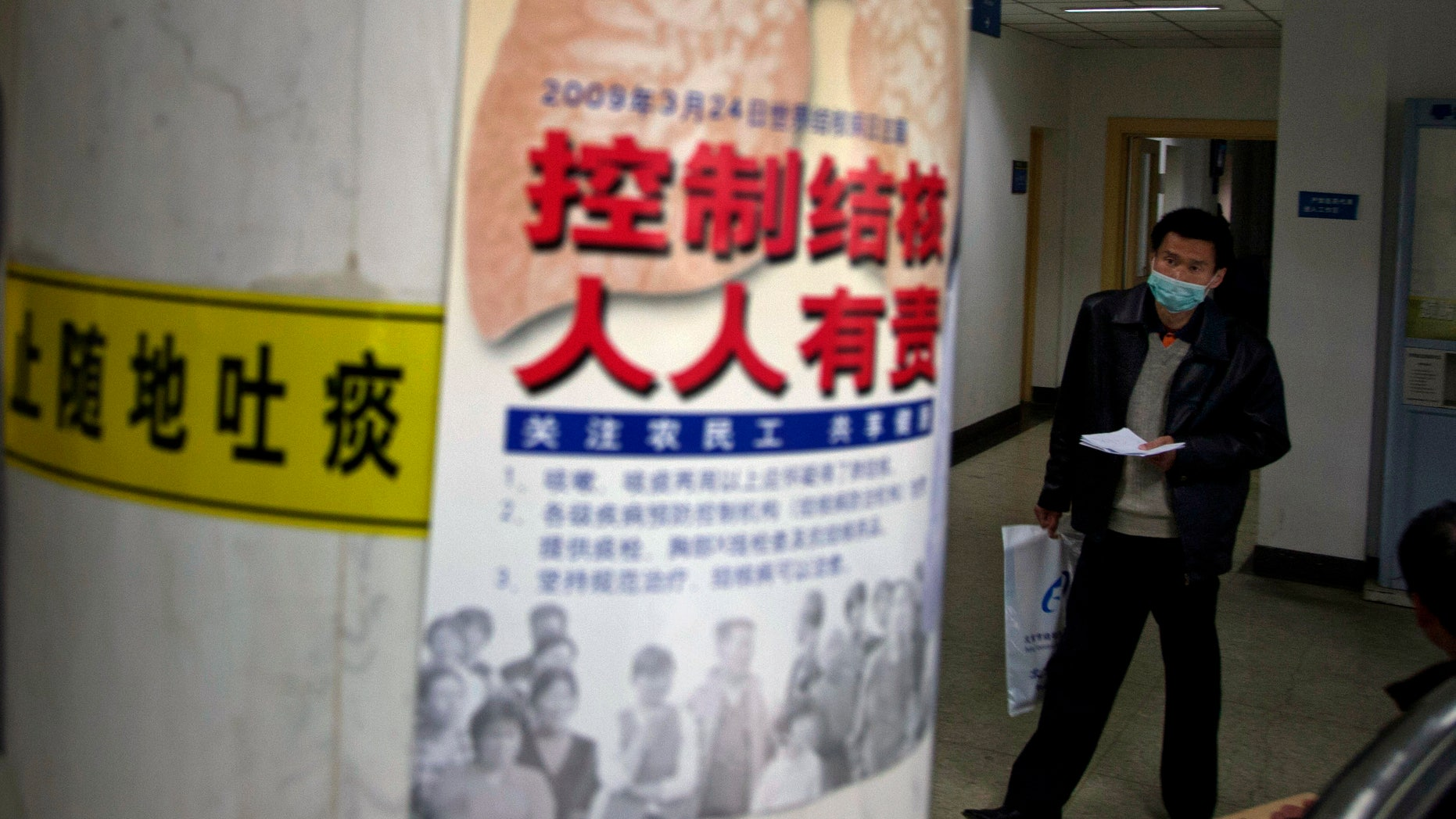 "A visitor wearing a mask walks near a poster promoting tuberculosis awareness which reads ""Control TB, Everyone's Duty"" and a yellow ""Do Not Spit"" sign at the Beijing Chest Hospital. (AP Photo/Ng Han Guan)"