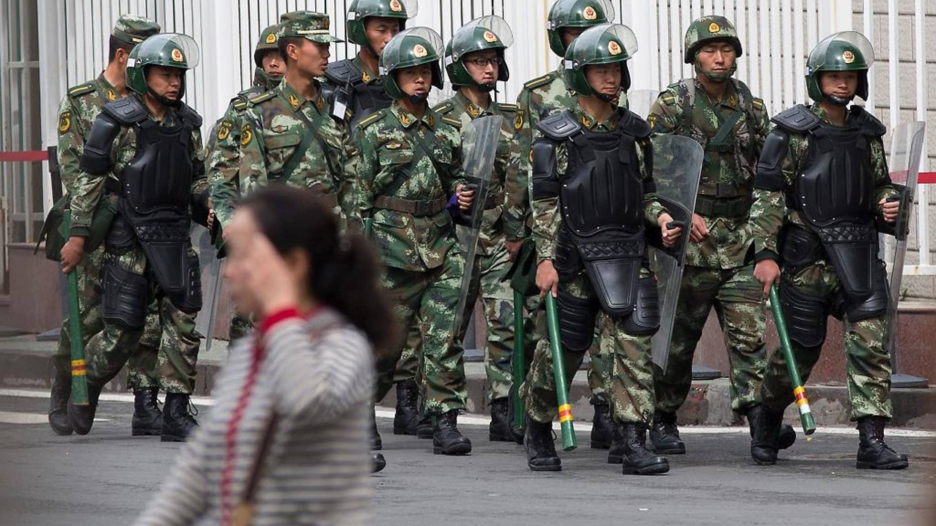 FILE - In this May 23, 2014 file photo, paramilitary policemen with shields and batons patrol near the People's Square in Urumqi, China's northwestern region of Xinjiang.  So far this month, police in China's restive western region of Xinjiang have broken up 23 terror and religious extremism groups and caught over 200 suspects, state media reported Monday, May 26. (AP Photo/Andy Wong, File)