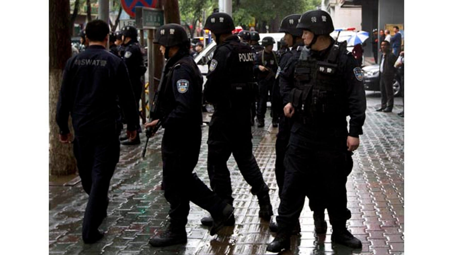 May 22, 2014: Armed policemen prepare to patrol near the site of an explosion in Urumqi, northwest China's Xinjiang Uygur Autonomous Region.  (AP Photo/Andy Wong)
