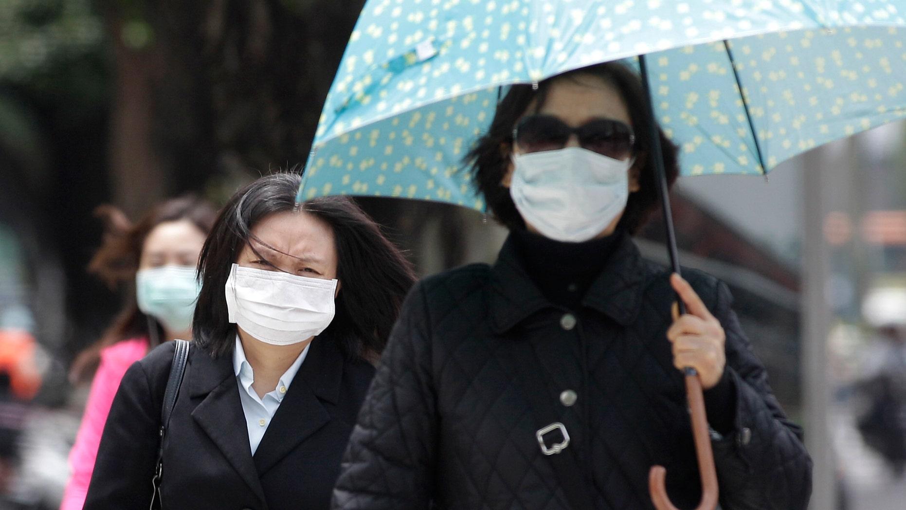 Pedestrians wearing medical masks walk on the street outside National Taiwan University Hospital in Taipei.