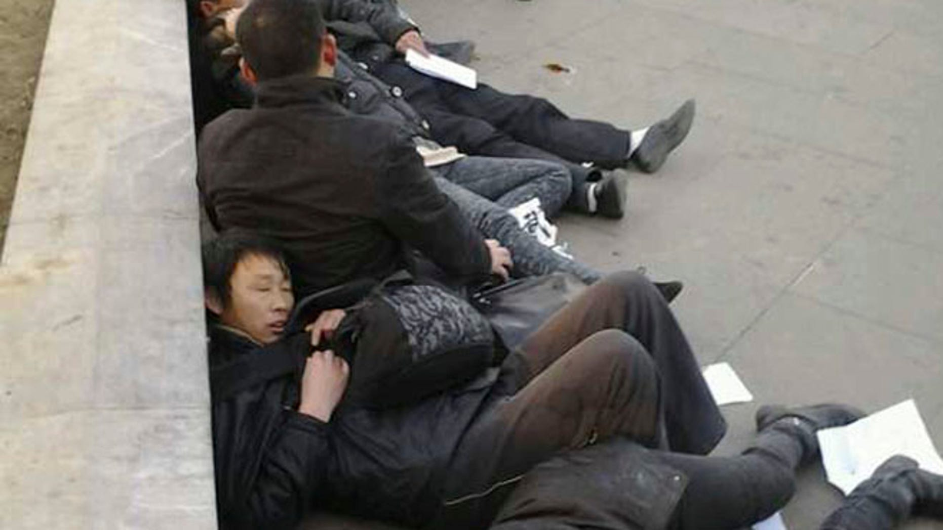 In this photo taken Dec. 10, 2013, which The Associated Press obtained on Wednesday, Dec. 11, 2013, from a friend of the petitioners, Chinese residents from Wuhan province lie on the ground after drinking pesticide near a historic watchtower in the heart of Beijing, China.  A dozen central Chinese city residents protesting the demolition of their homes drank pesticide in Beijing in a desperate bid for attention that underscores the failures of a decades-old petitioning system. The photo has been authenticated based on its contents and other AP reporting.