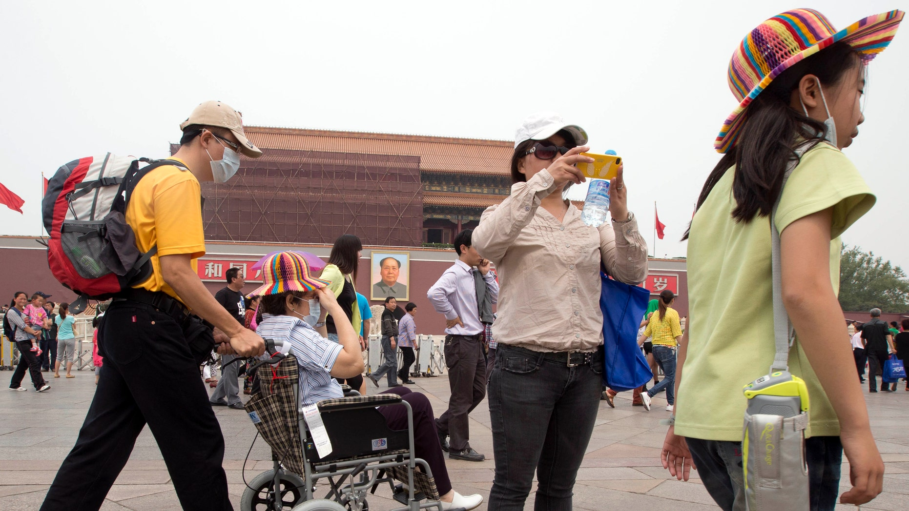 In this Tuesday, May 7, 2013 photo, visitors to Tiananmen Gate wear masks during a day of heavy pollution in Beijing.