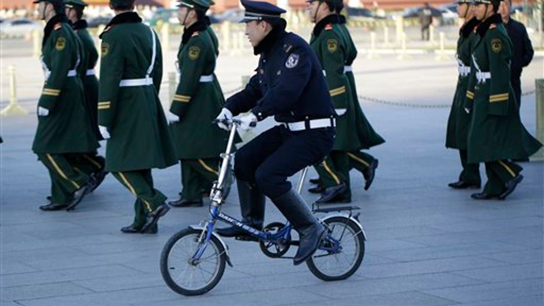 Nov. 13, 2012: Chinese paramilitary policemen march as police officer rides a bicycle during the 18th Chinese Communist Party Congress in Tiananmen Square.