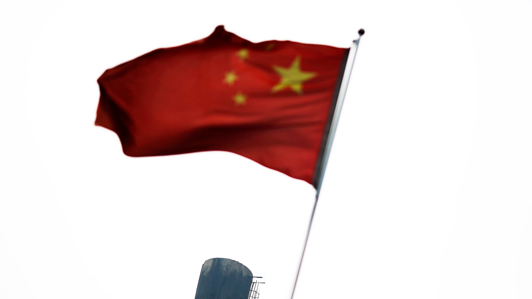 A Chinese national flag is seen in front of the chimney of a heat supply plant in Beijing July 16, 2014.