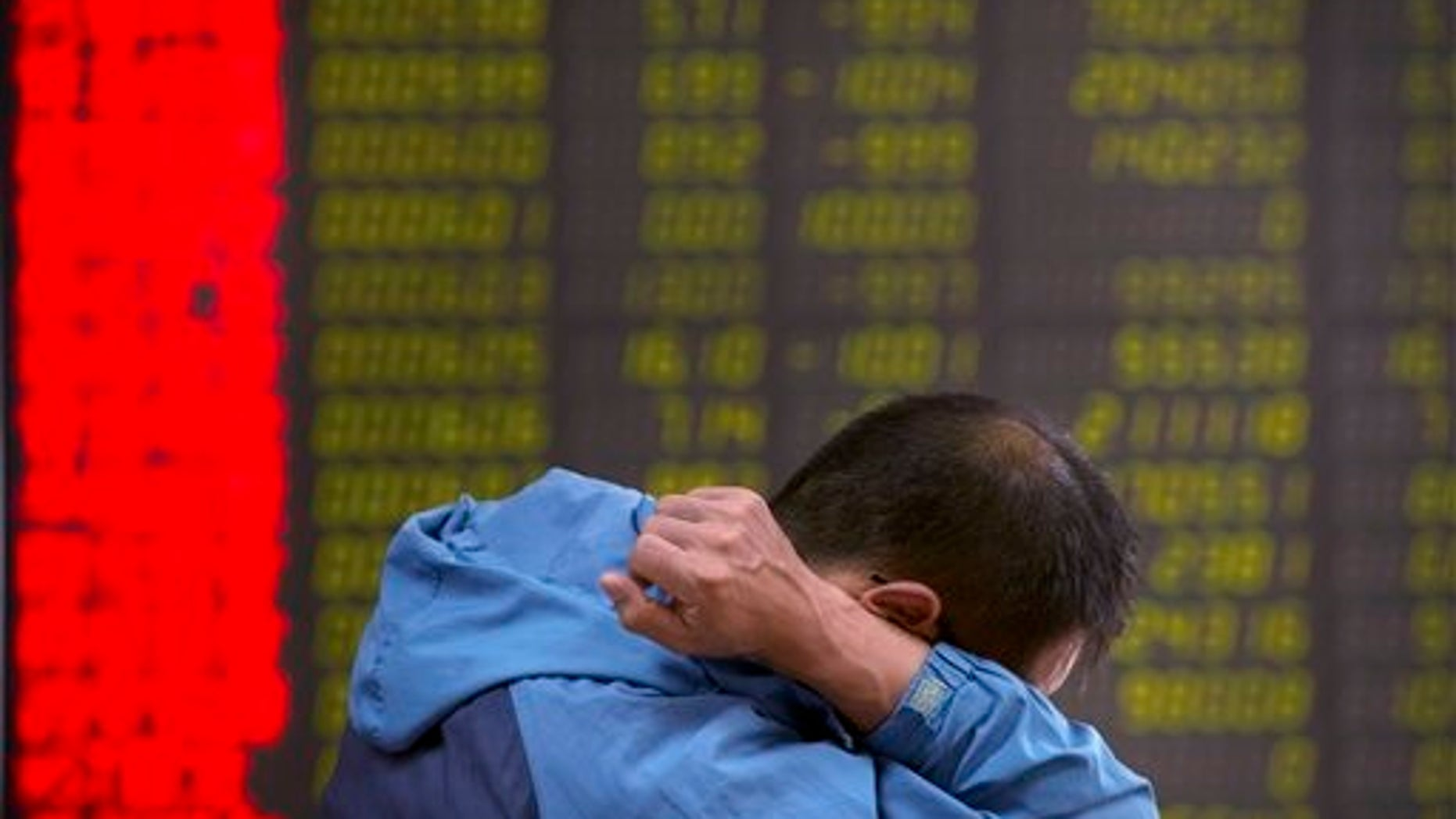 A Chinese investor monitors stock prices at a brokerage house in Beijing, Tuesday, Aug. 25, 2015.  China's main stock market index has fallen for a fourth day, plunging 7.6 percent to an eight-month low.  (AP Photo/Mark Schiefelbein)