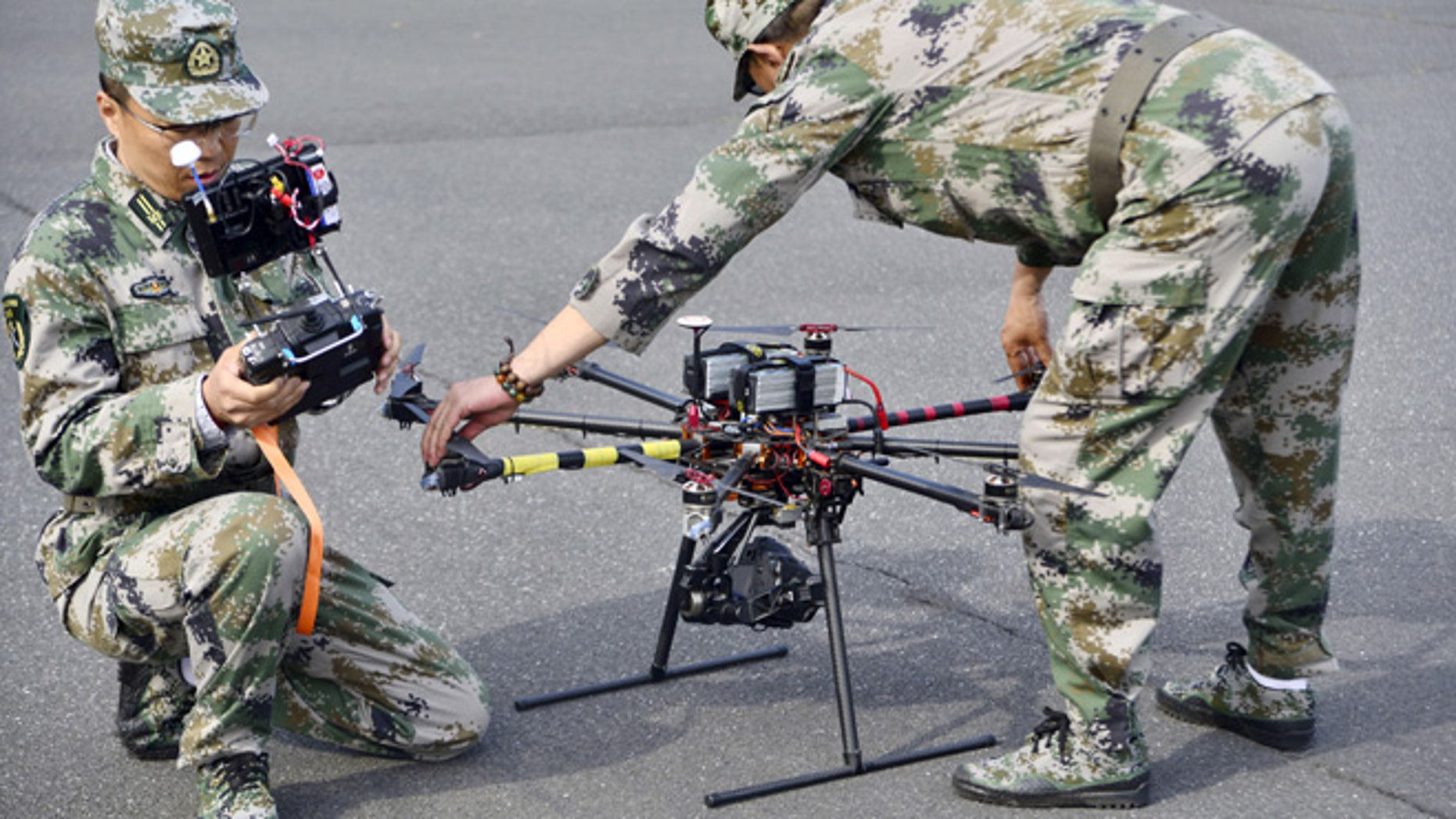 April 21, 2015: A pair of militia members prepare to fly drones during a test in Shanghai, China.