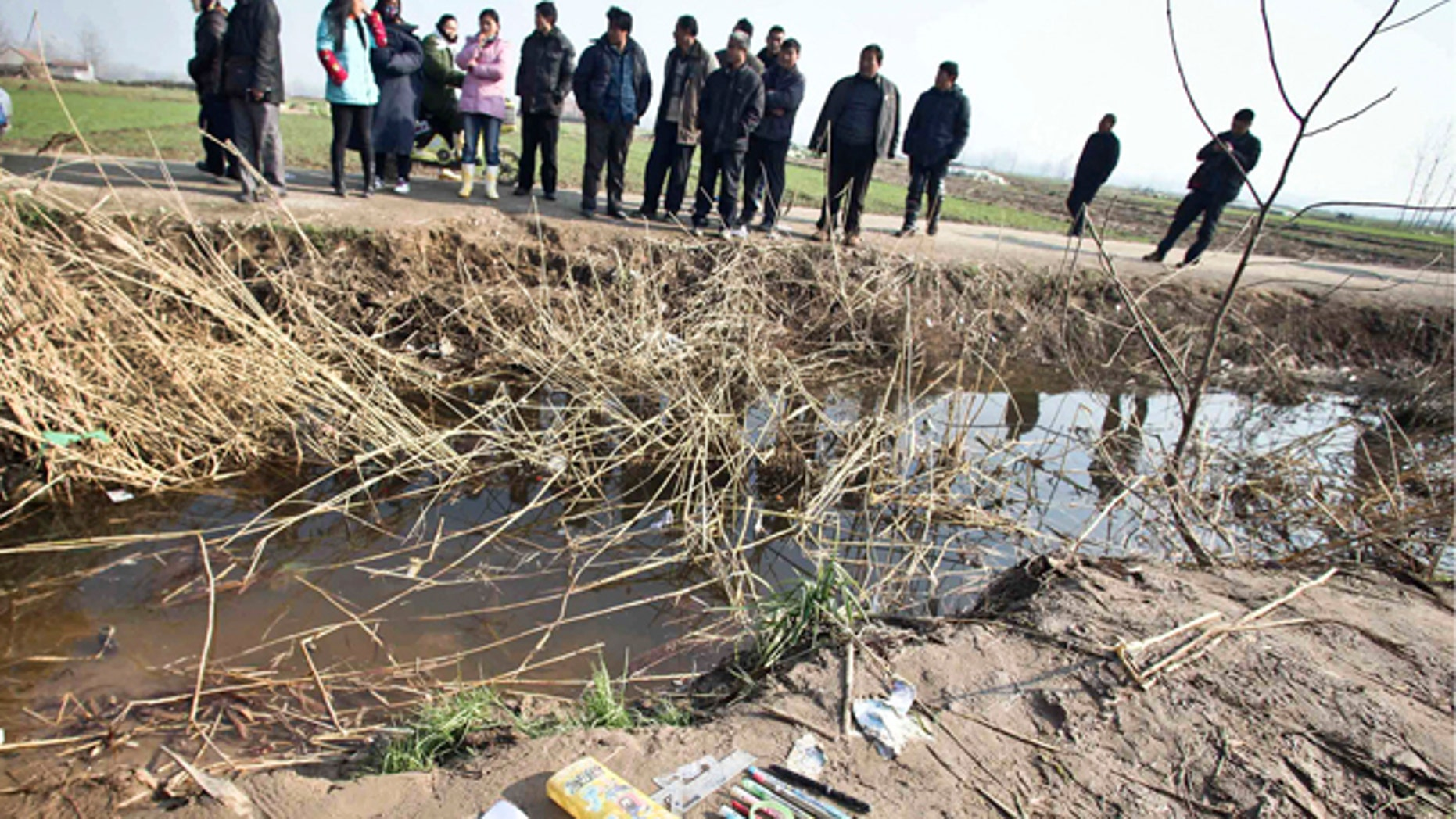 Dec. 13: People look at the accident site of a school bus which veered into a water-filled ditch, in Feng county in east China's Jiangsu province.