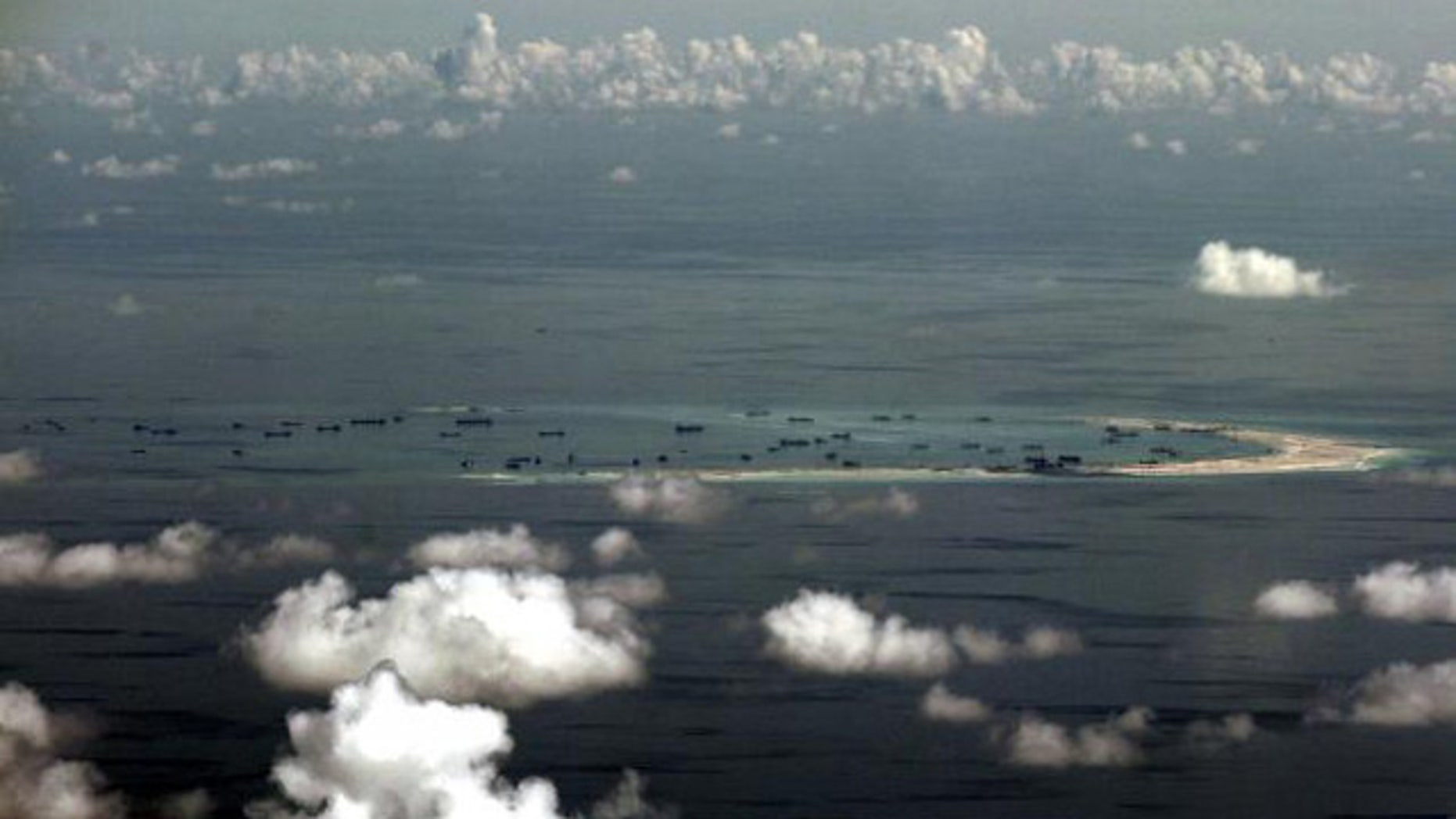 May 11, 2015: An aerial photo taken though a glass window of a Philippine military plane shows alleged on-going land reclamation by China on Mischief Reef in the Spratly Islands in the South China Sea, west of Palawan, Philippines. (REUTERS/RITCHIE B. TONGO)