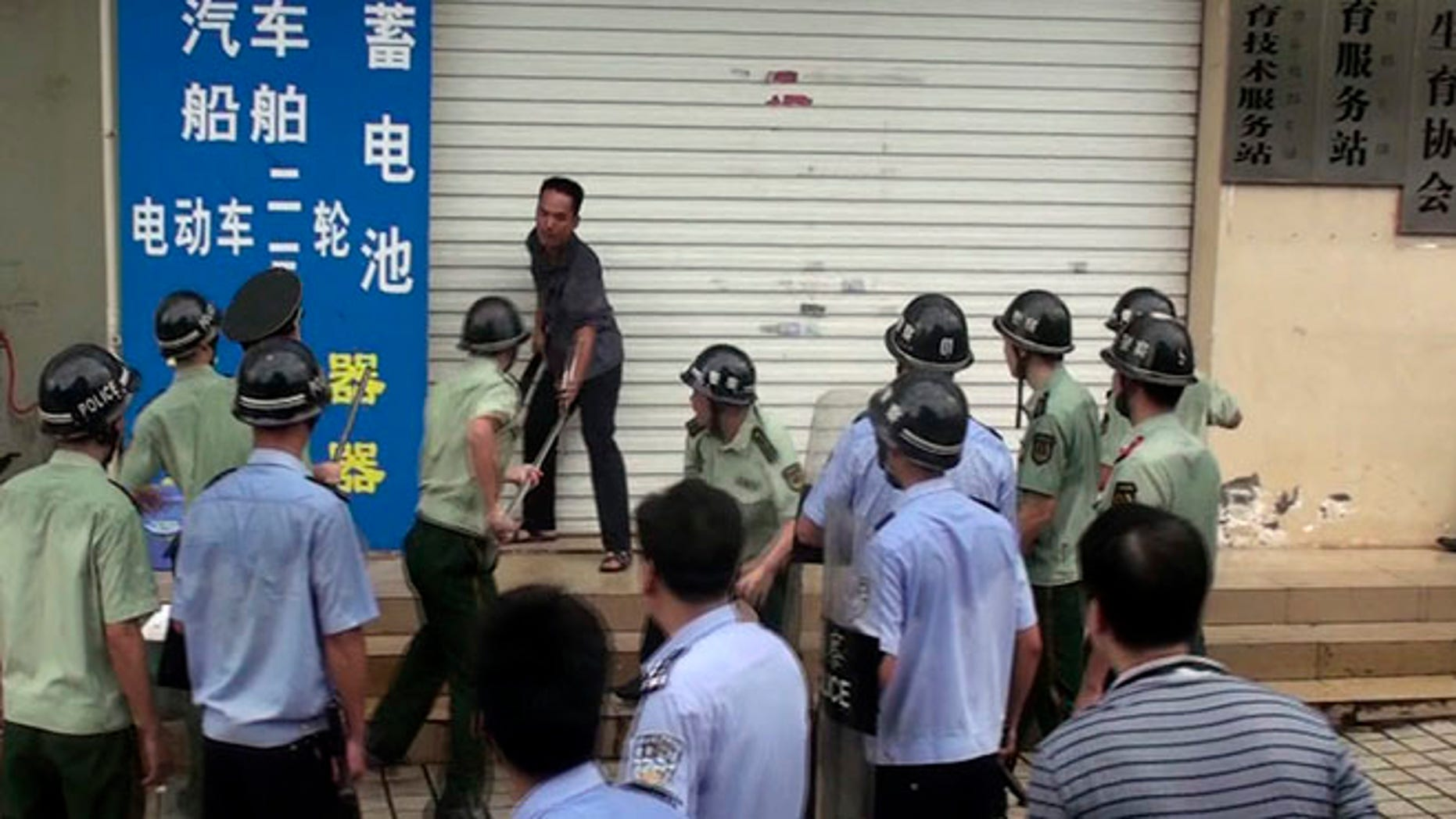 In this  July 23, 2013 photo, Chinese security personnel try to subdue a knife-wielding man outside the family planning office in Dongxing city in southwest China's Guangxi province. Local media report that the man attacked the local family planning office killing two officials and injuring another four after being refused a residency permit for his fourth child that he fathered in violation of China's one-child policy. (AP Photo) CHINA OUT